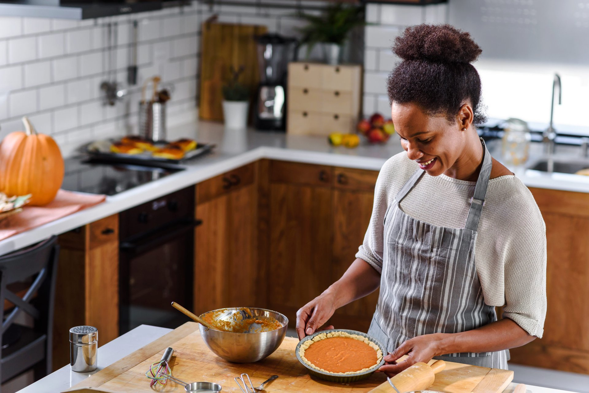 Woman preparing pumpkin pie for holidays