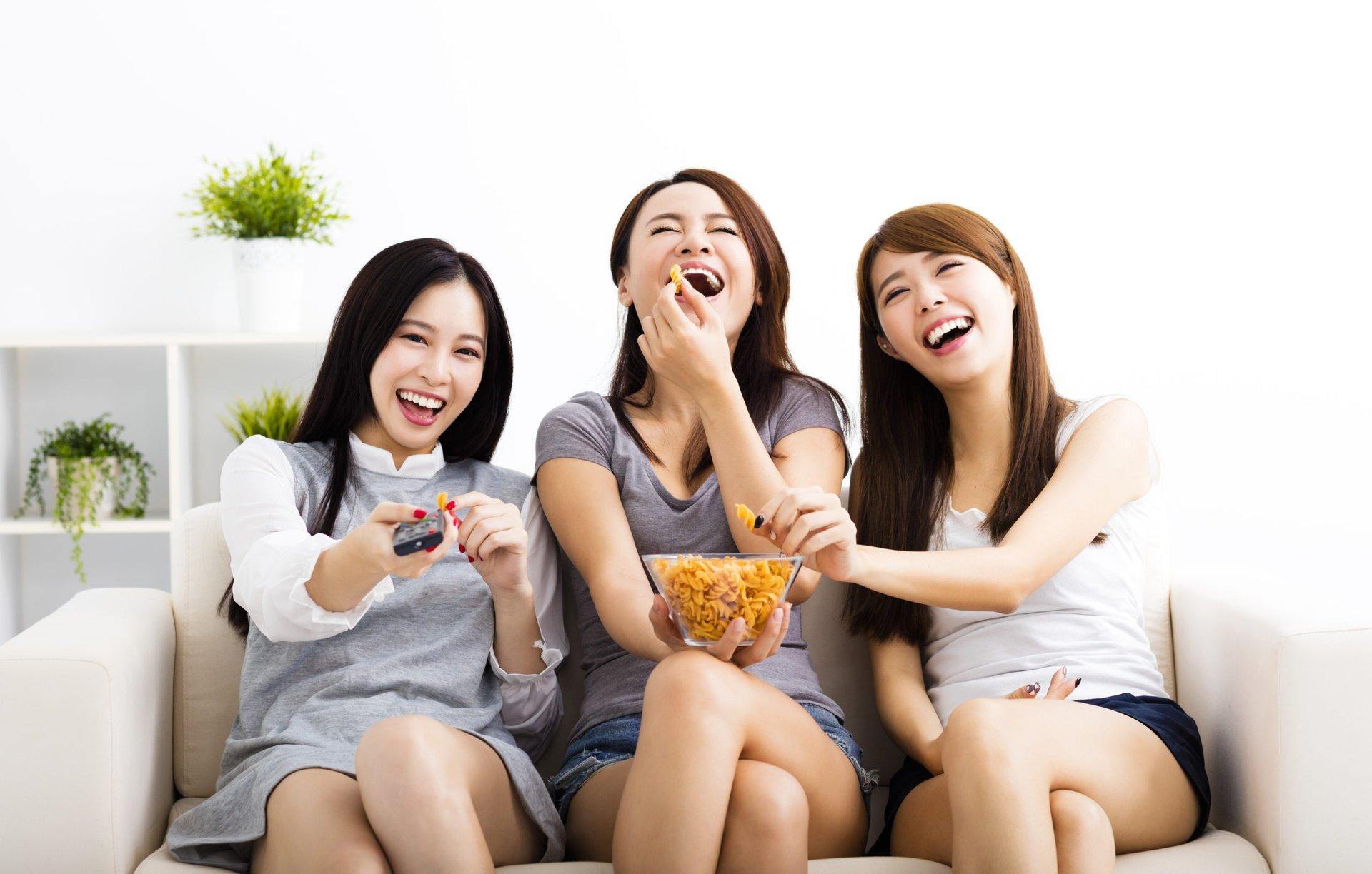 Three women friends watching TV