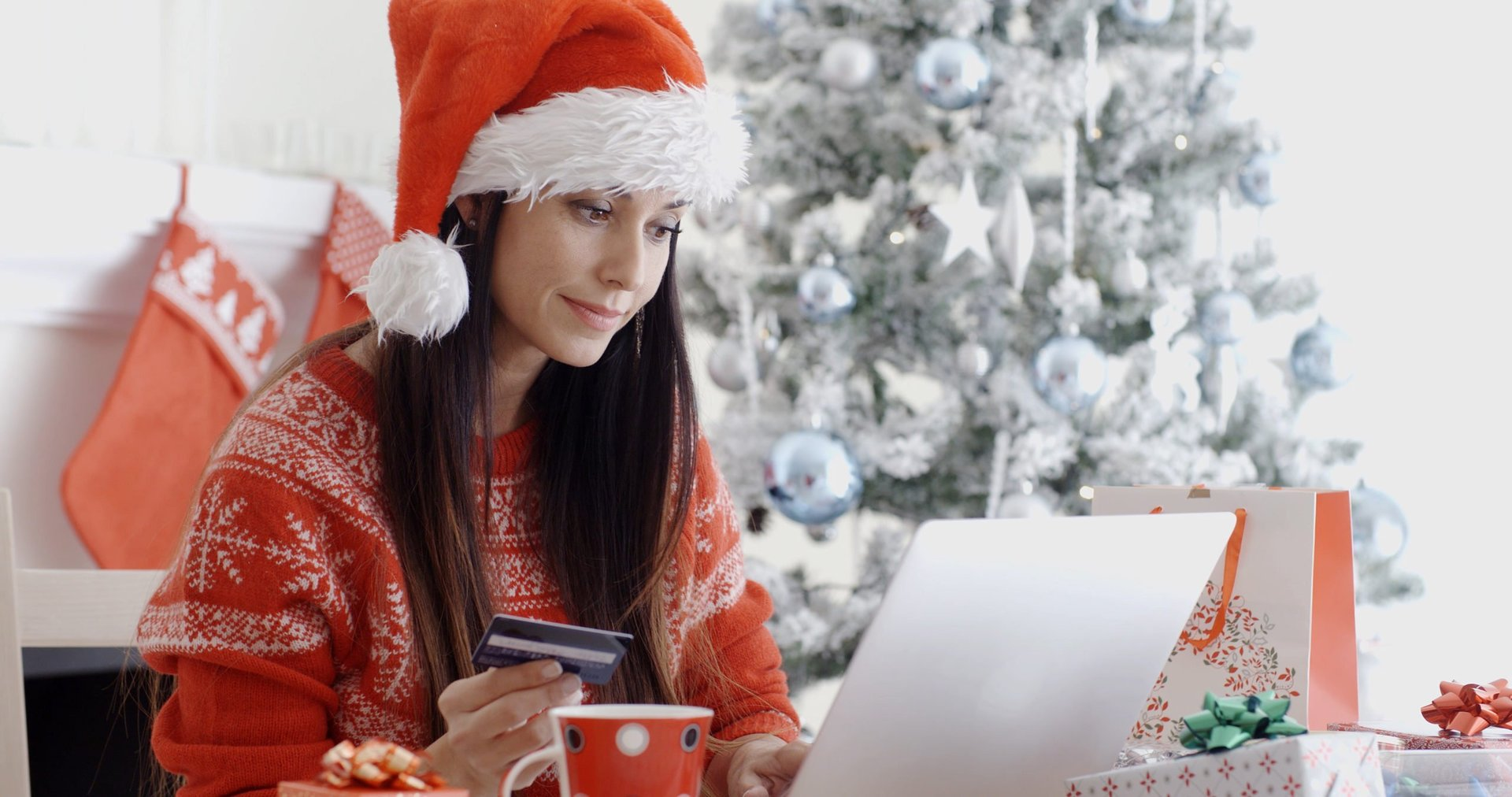 Happy woman using credit card for holiday shopping