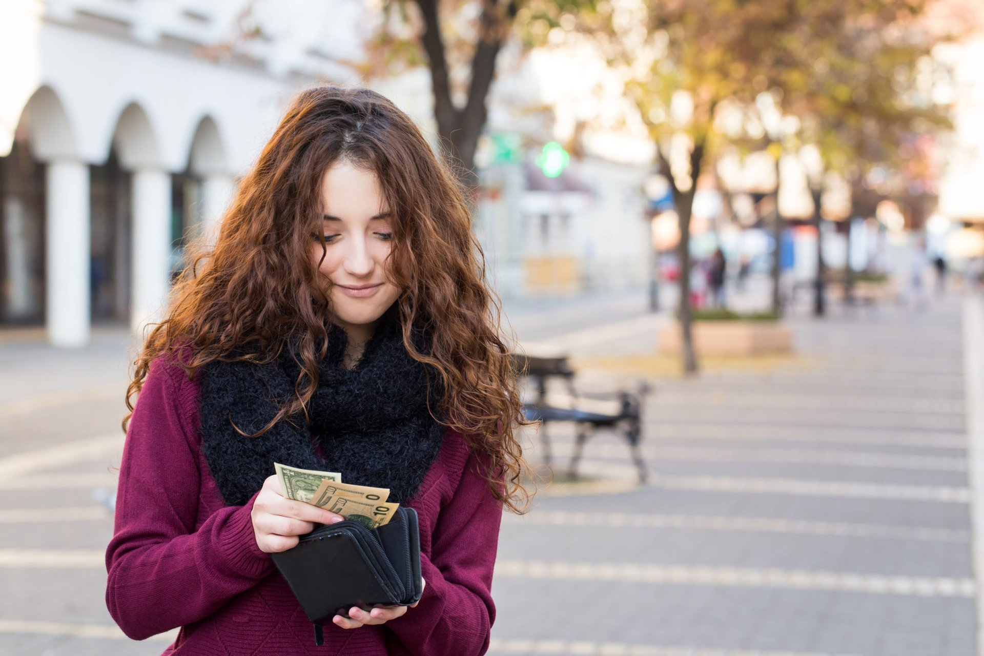 Young woman counts the cash in her wallet from her pay raise