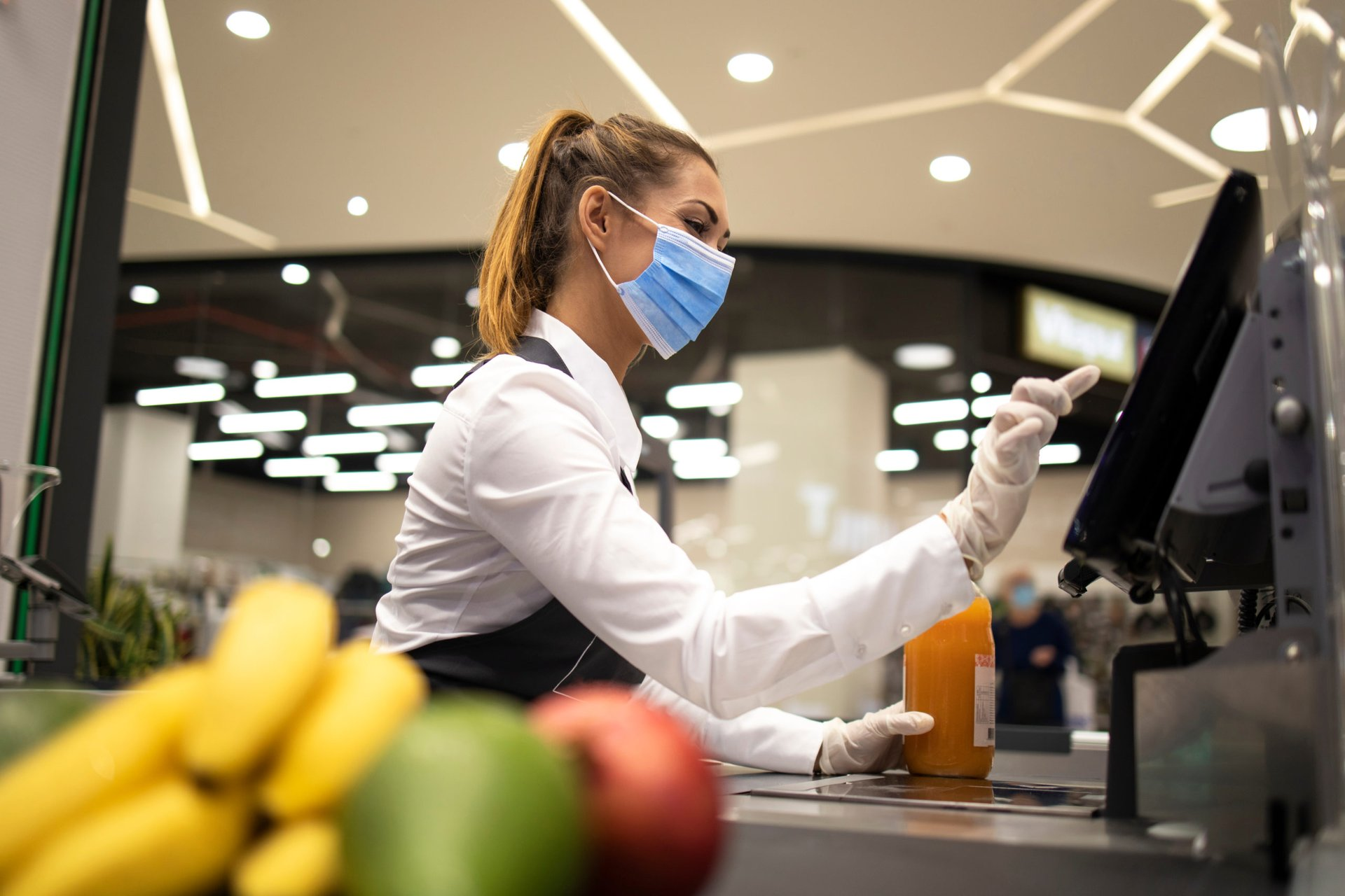 Grocery store cashier working in a mask and gloves