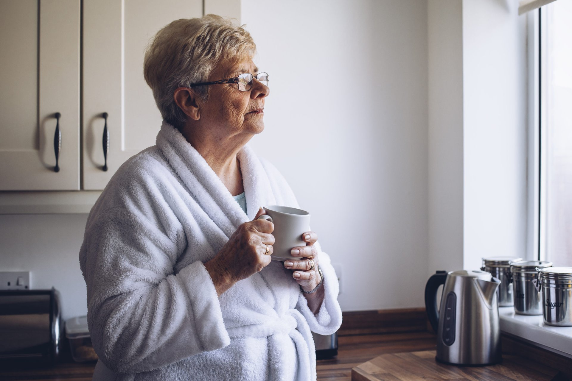 Sad senior woman drinking coffee