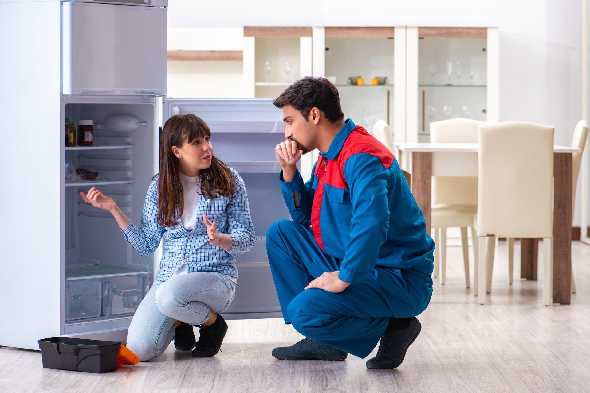 Repairman looking at a broken fridge