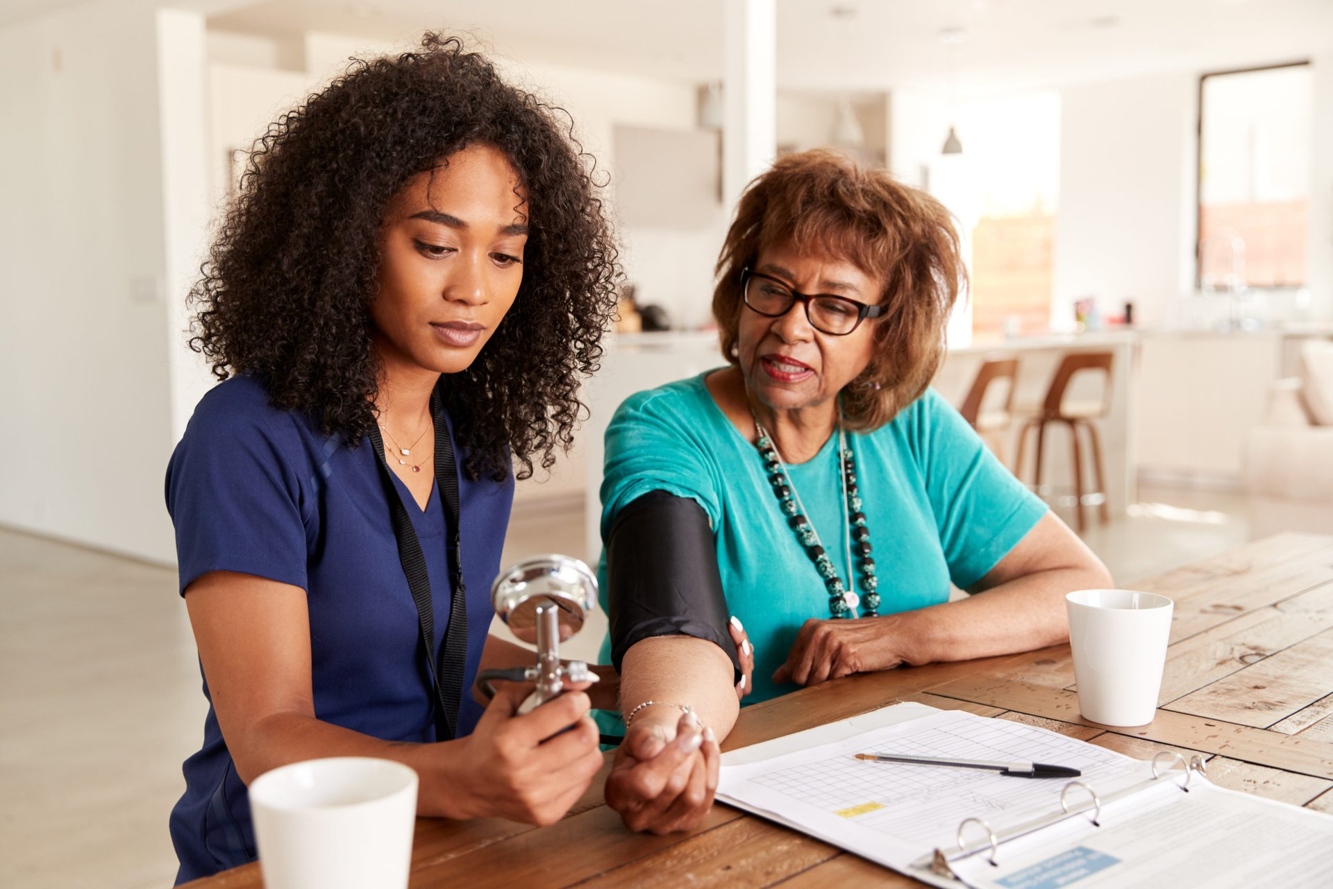 Home health aide taking a patient's blood pressure