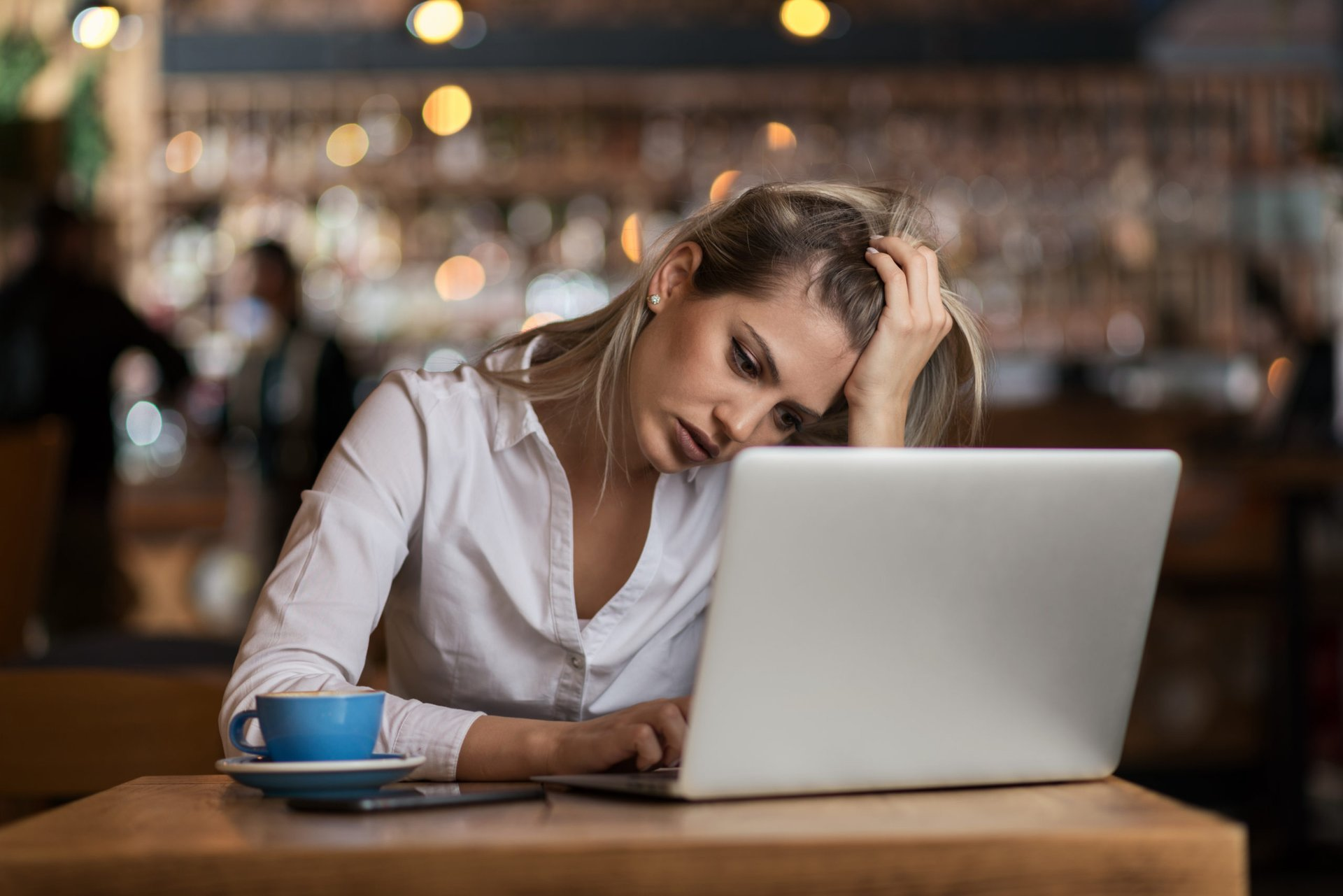 Stressed woman working on a laptop in a coffee shop