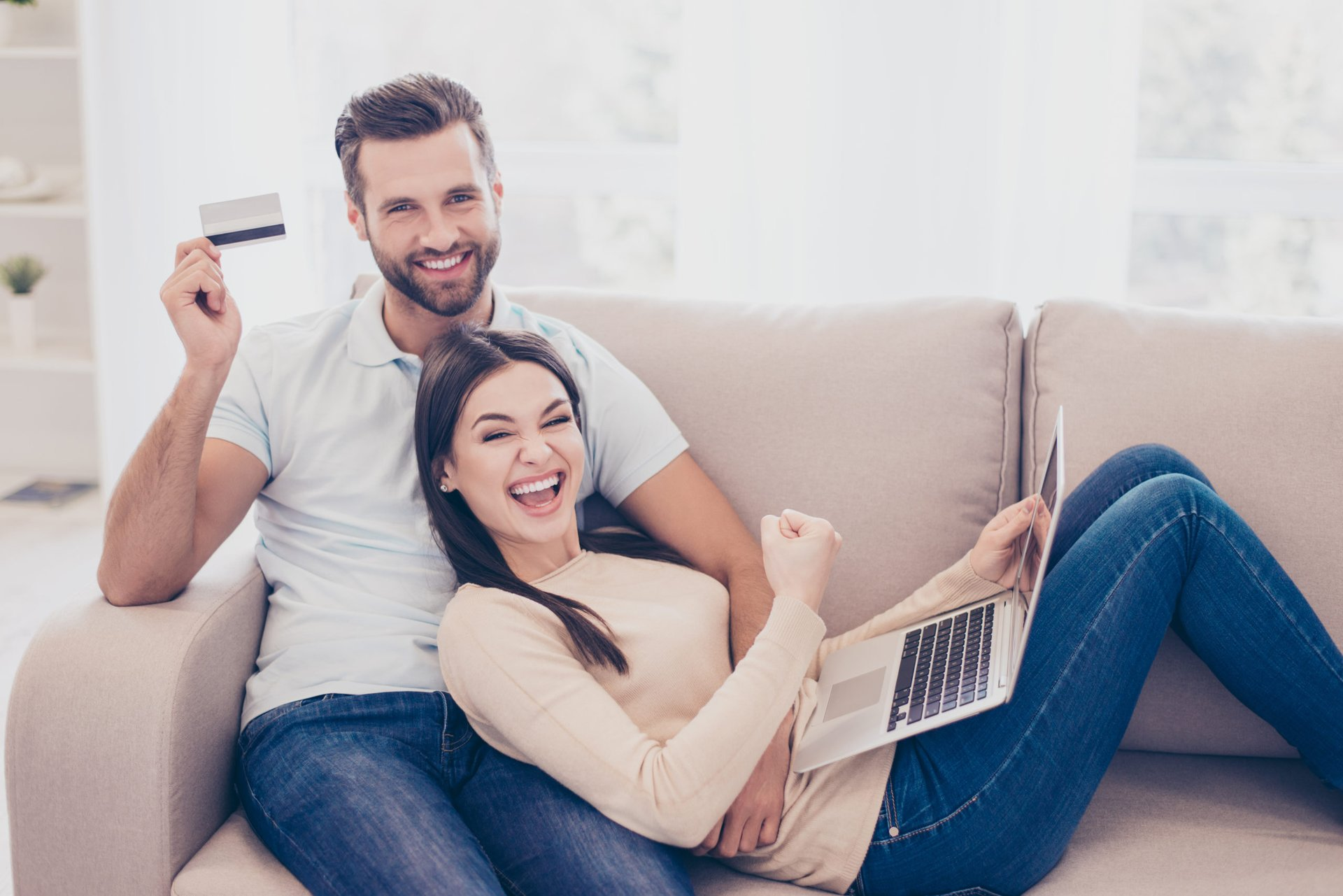 Couple excitedly booking travel on laptop with their credit card