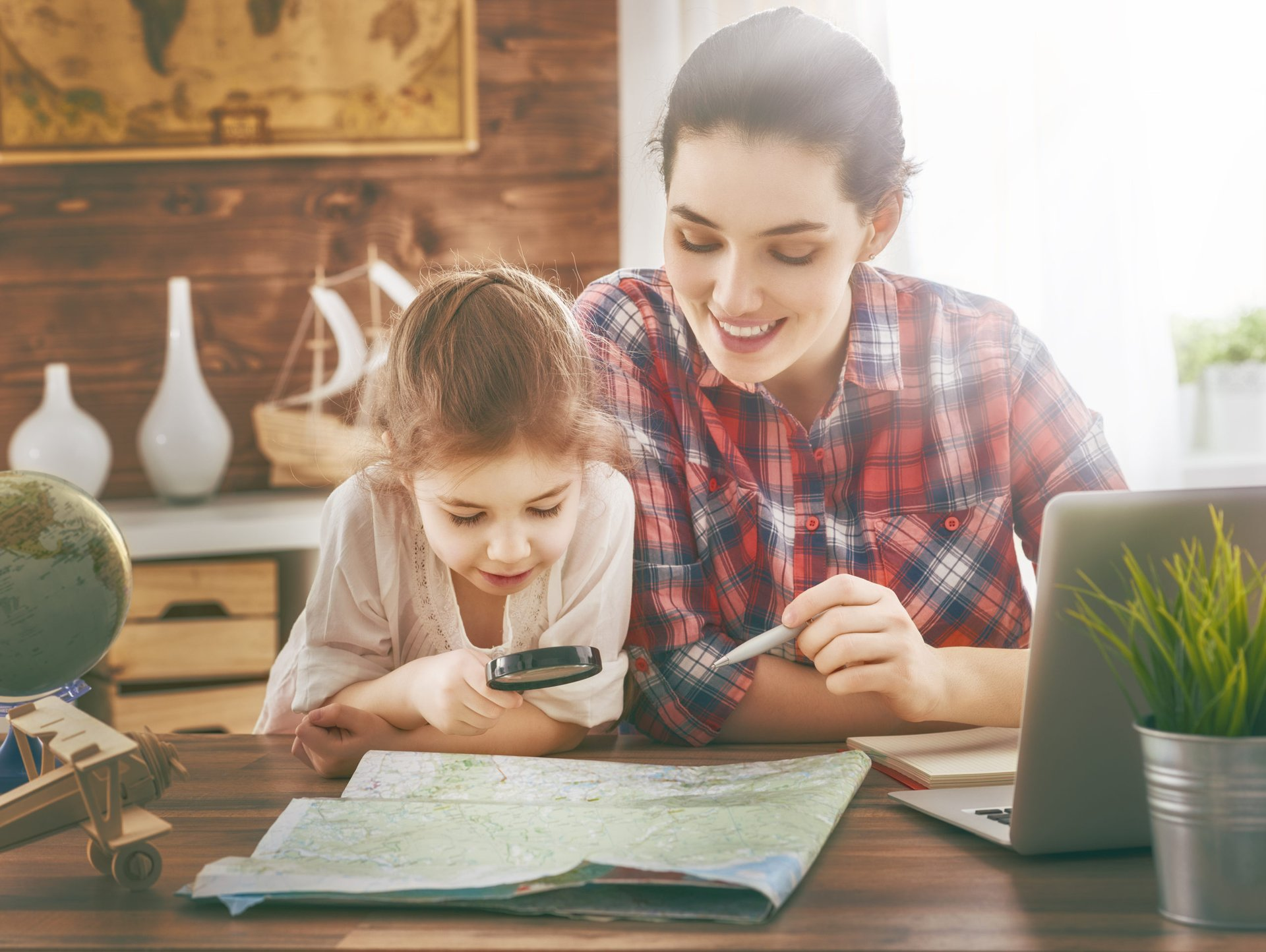 Mother and daughter planning travel and vacation on a map