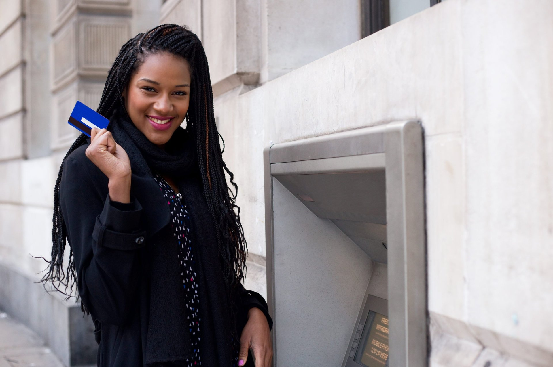 Woman using a debit card at an ATM
