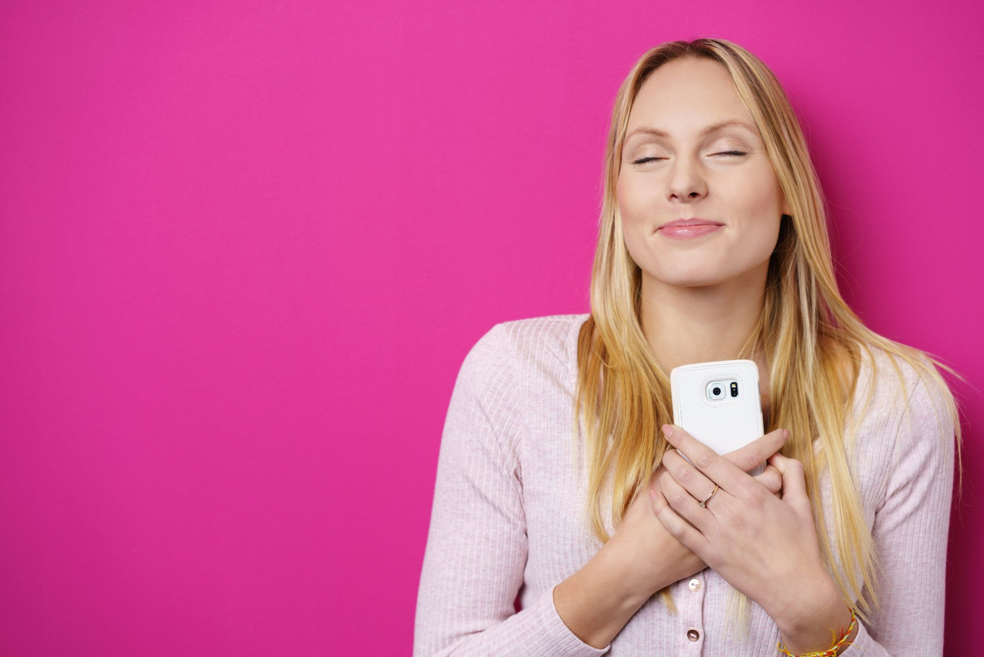 Happy and peaceful woman holding her phone