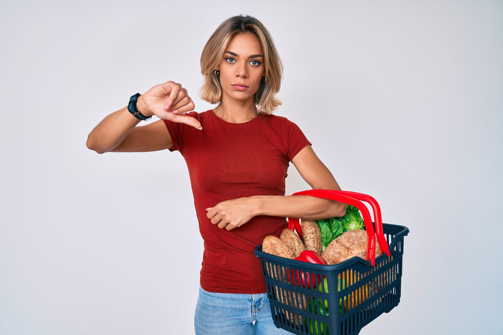 Woman with a basket of groceries giving thumbs down