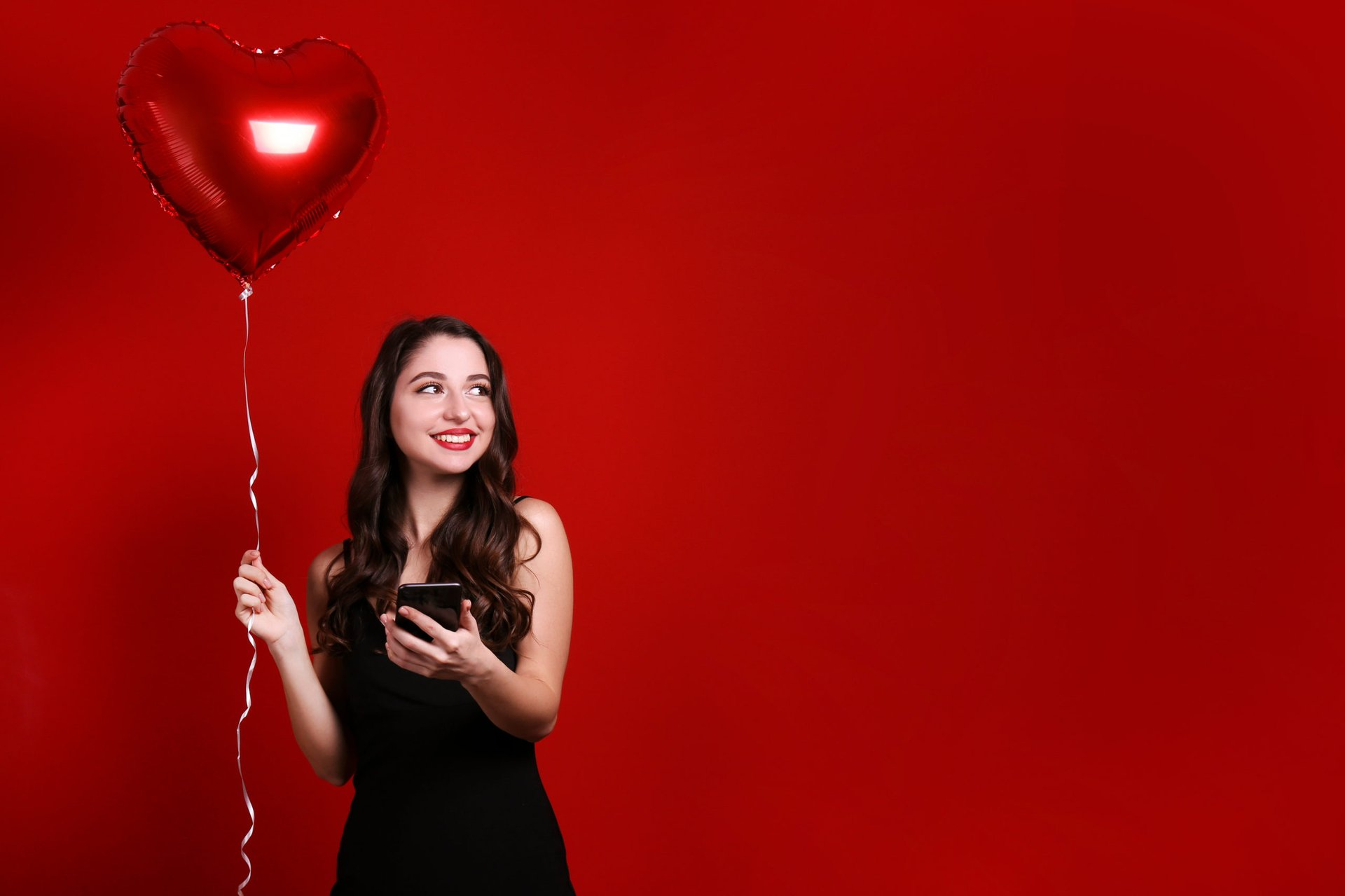 Woman with cell phone and a heart balloon