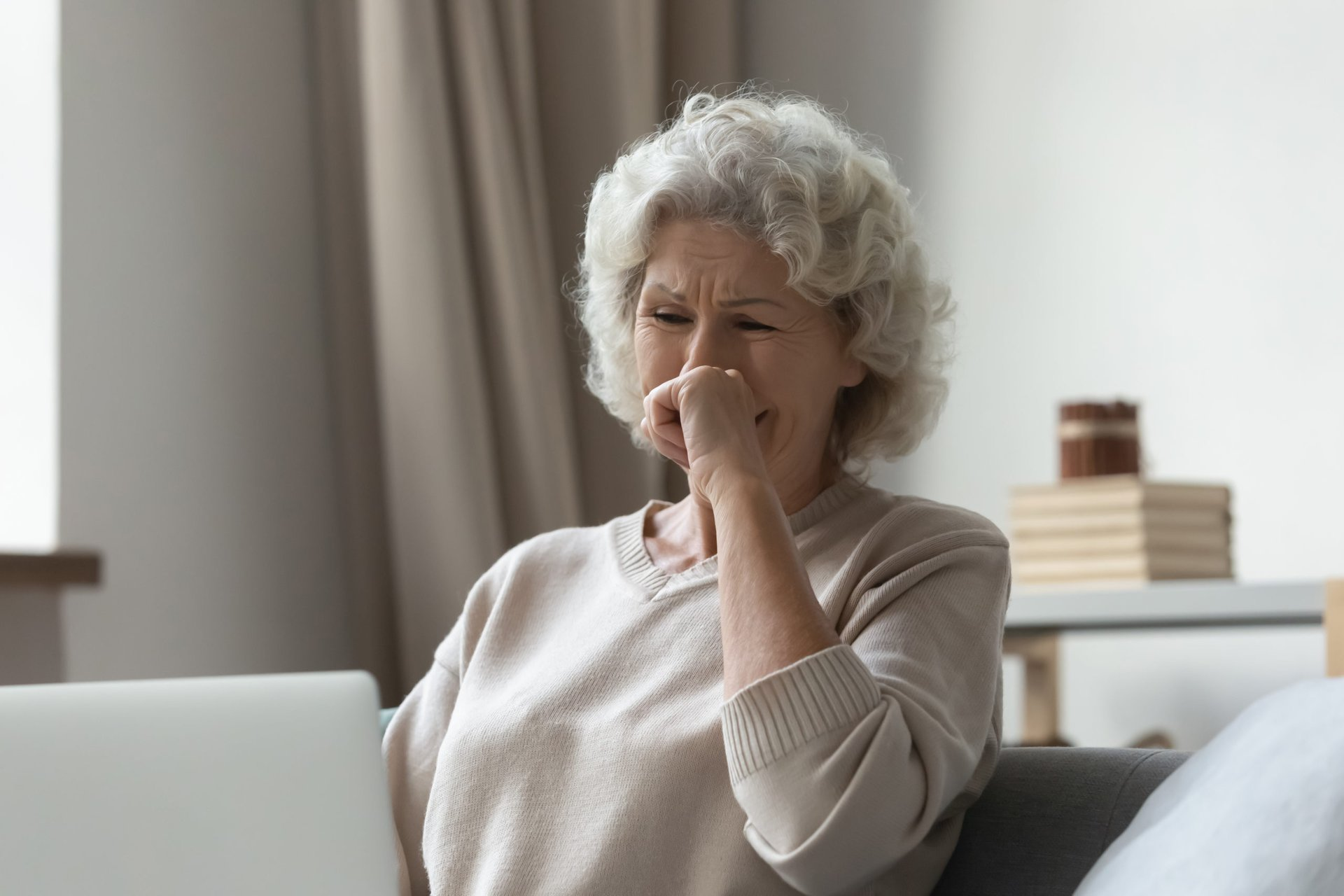 Upset senior on a laptop