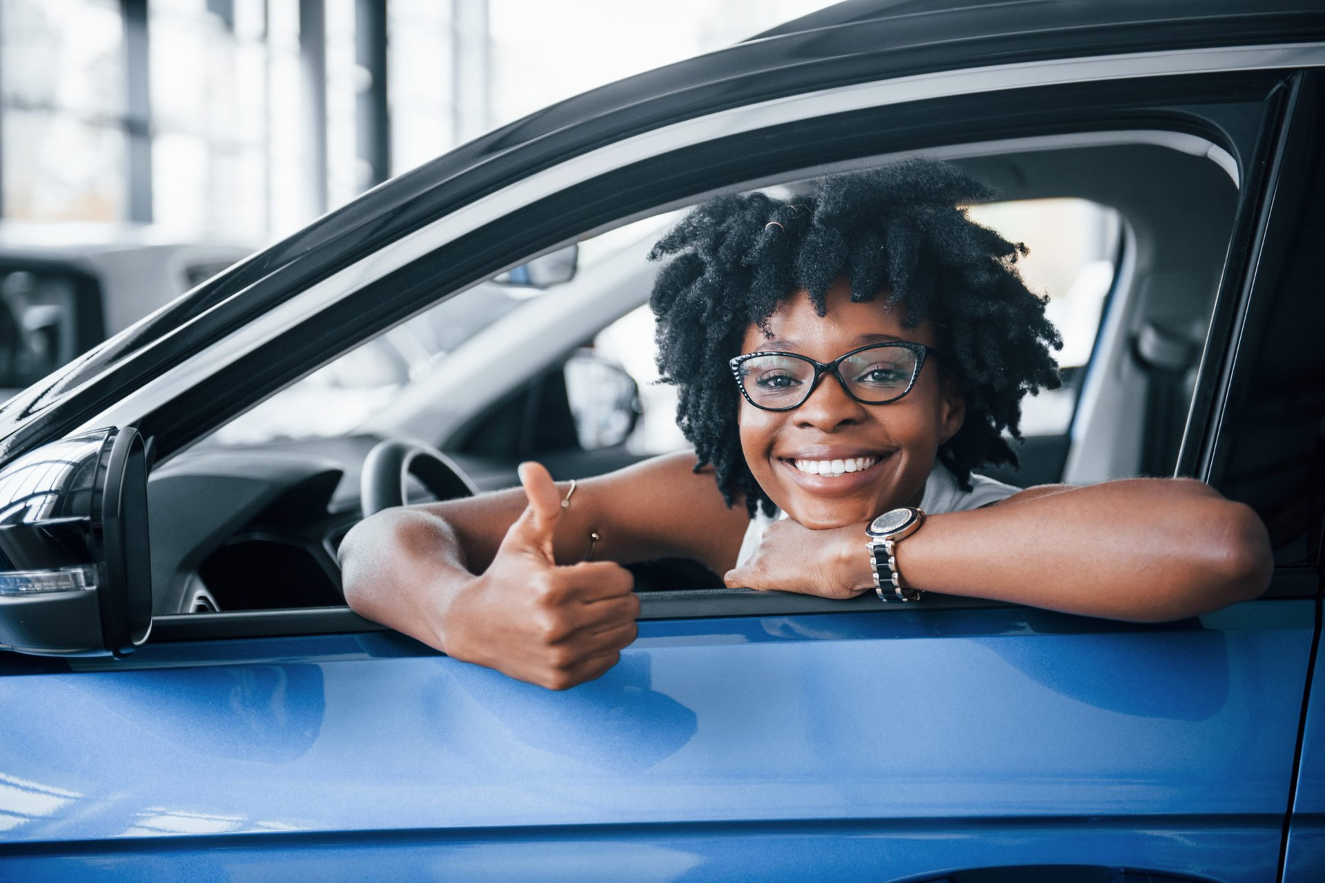 Woman driving car and giving thumbs up