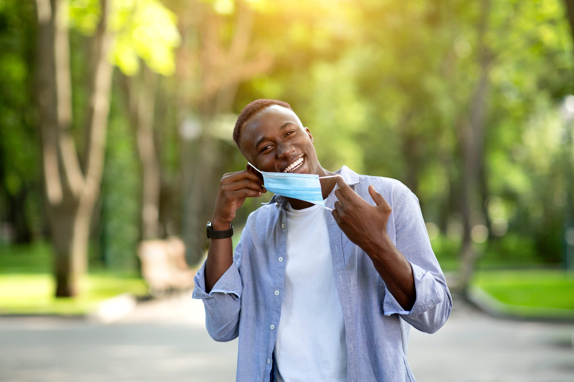 Man removing his mask outdoors