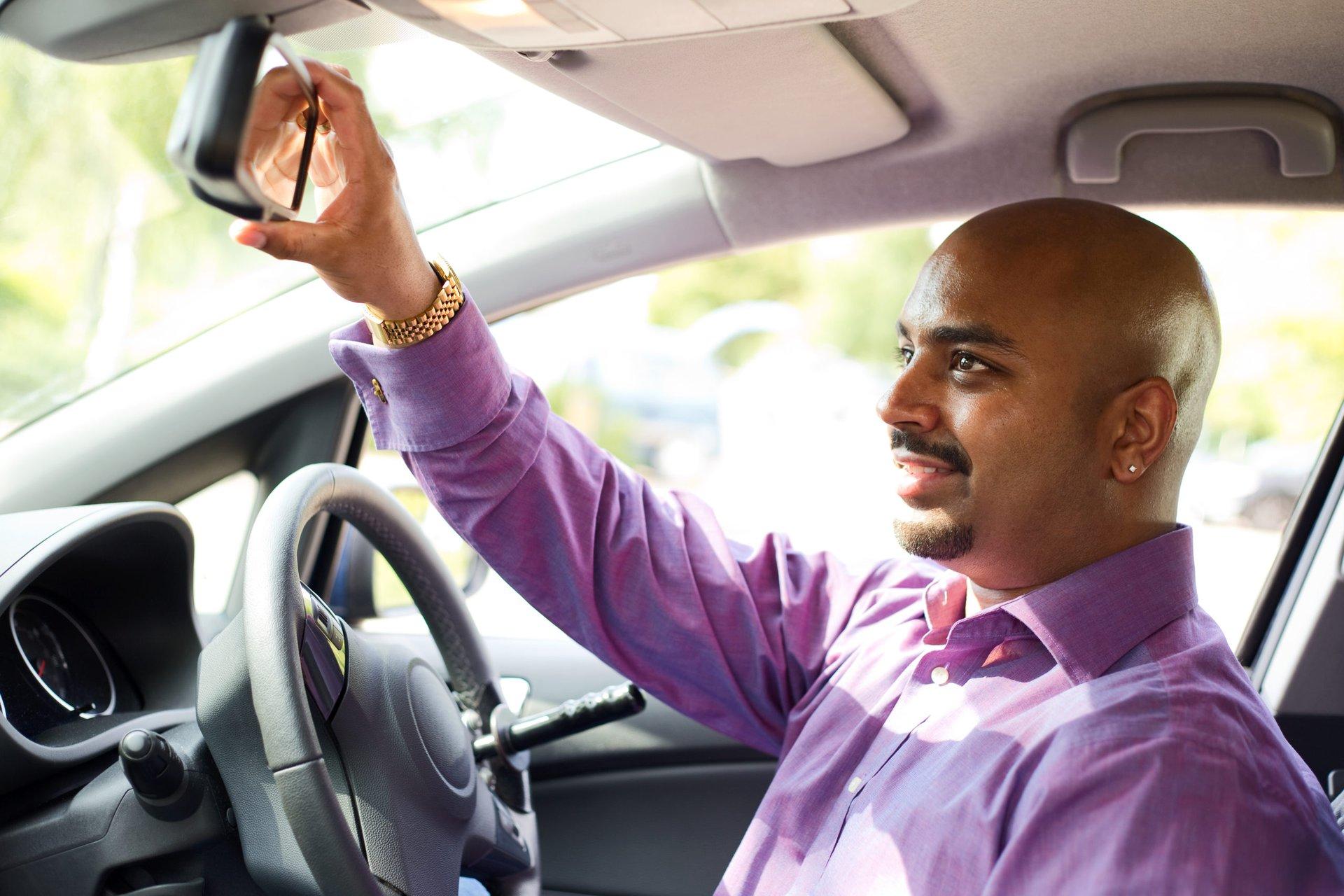 Driver adjusting his mirror