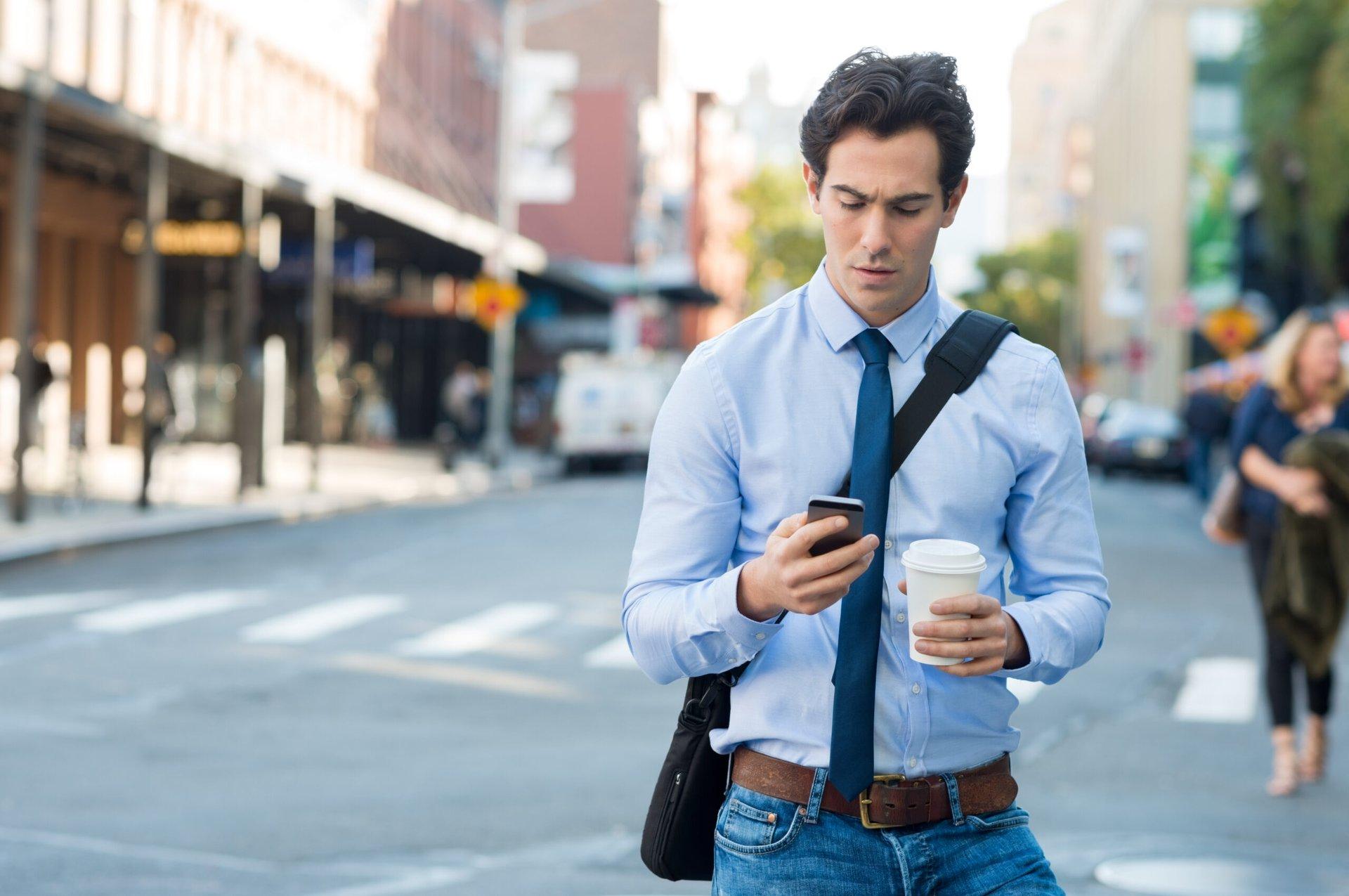 Man walking and looking at his phone