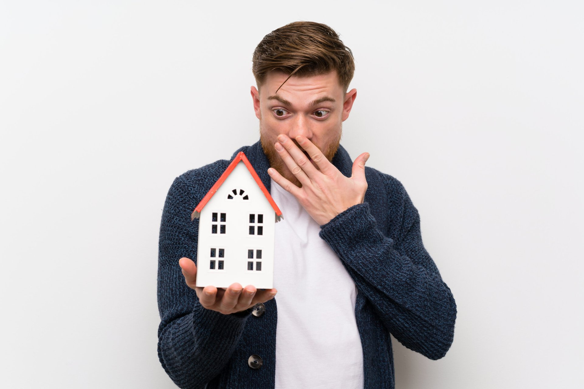 Worried man holding small house