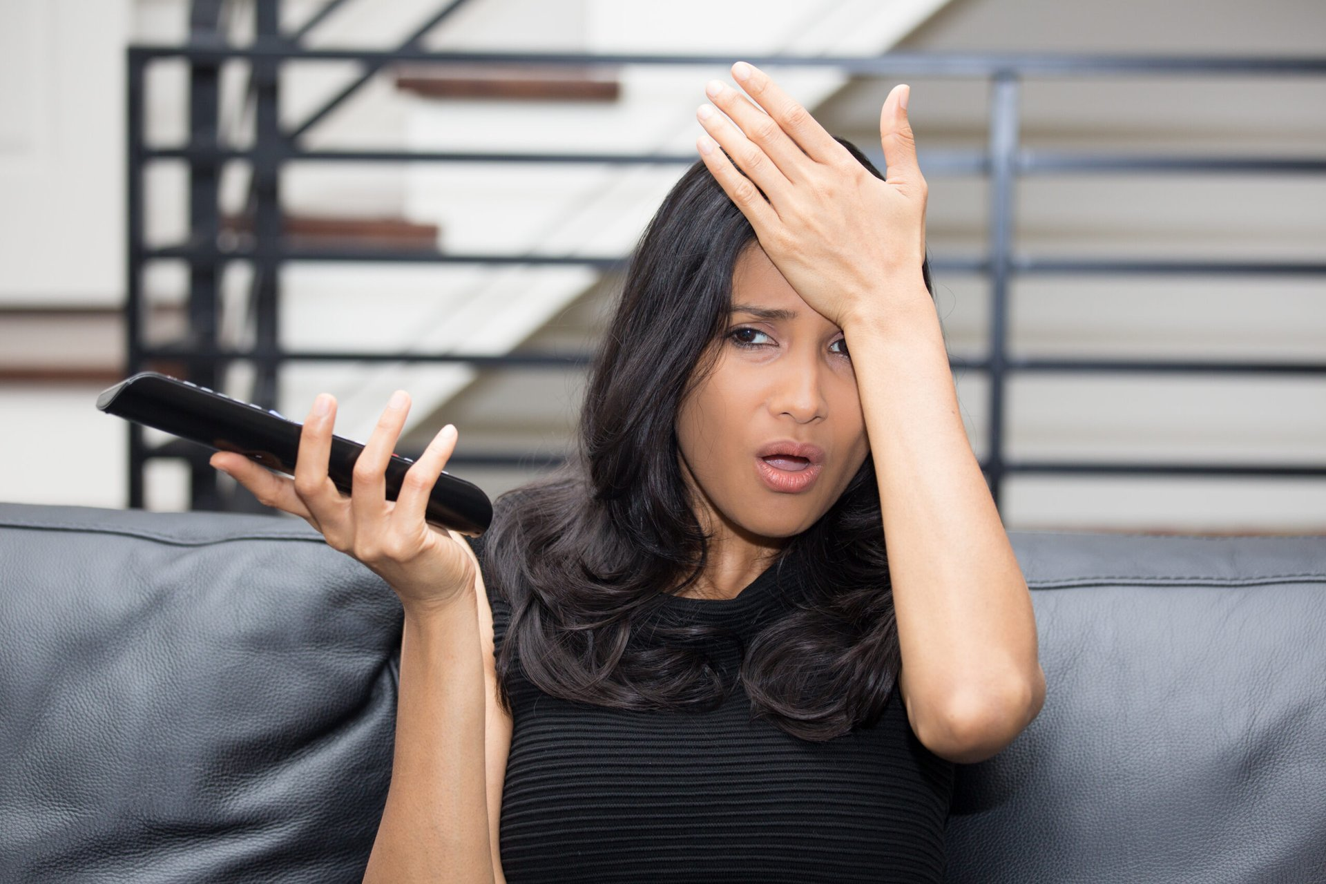 Unhappy woman watching TV