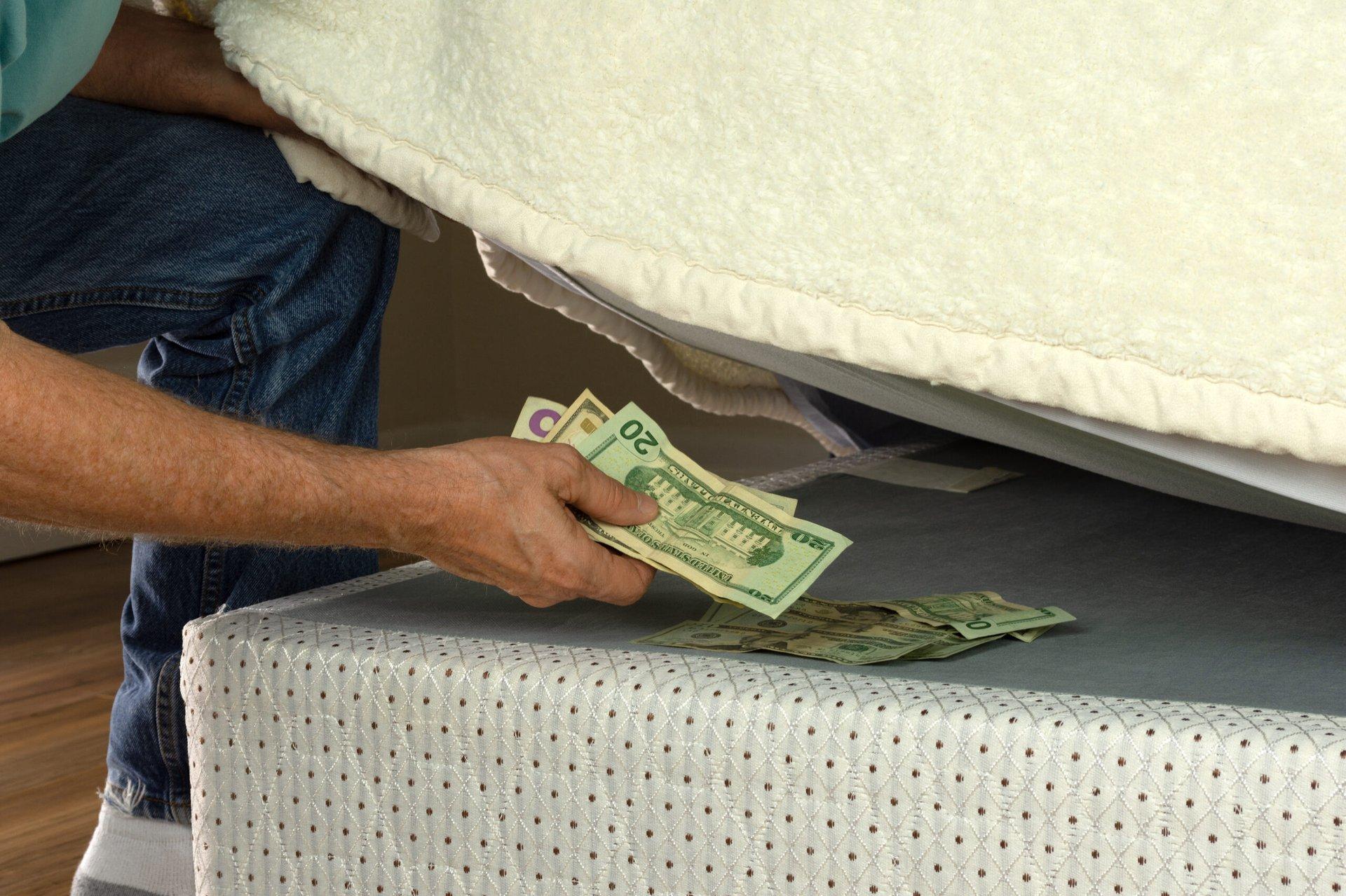 Man hiding cash under a mattress