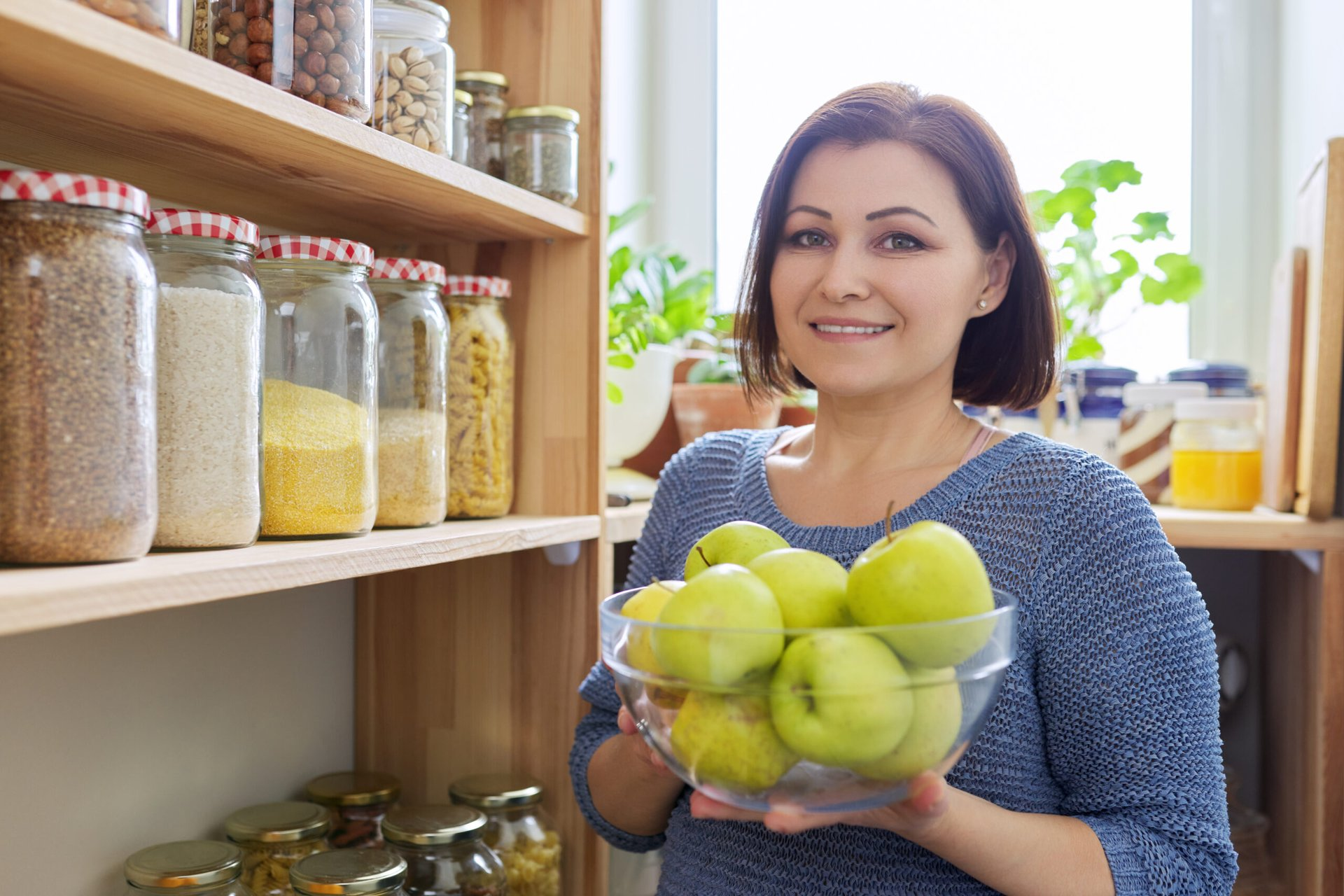 Woman adding fruit to her pantry