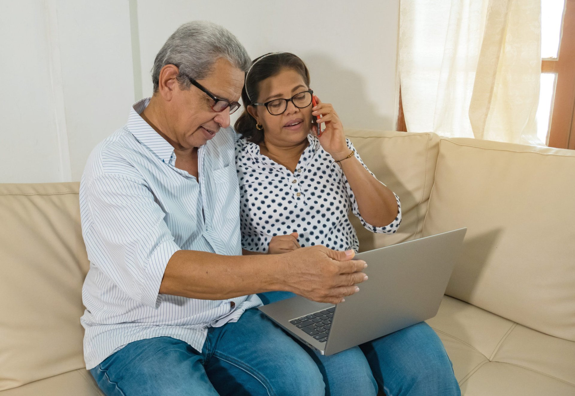 Older couple surfing the internet on a laptop