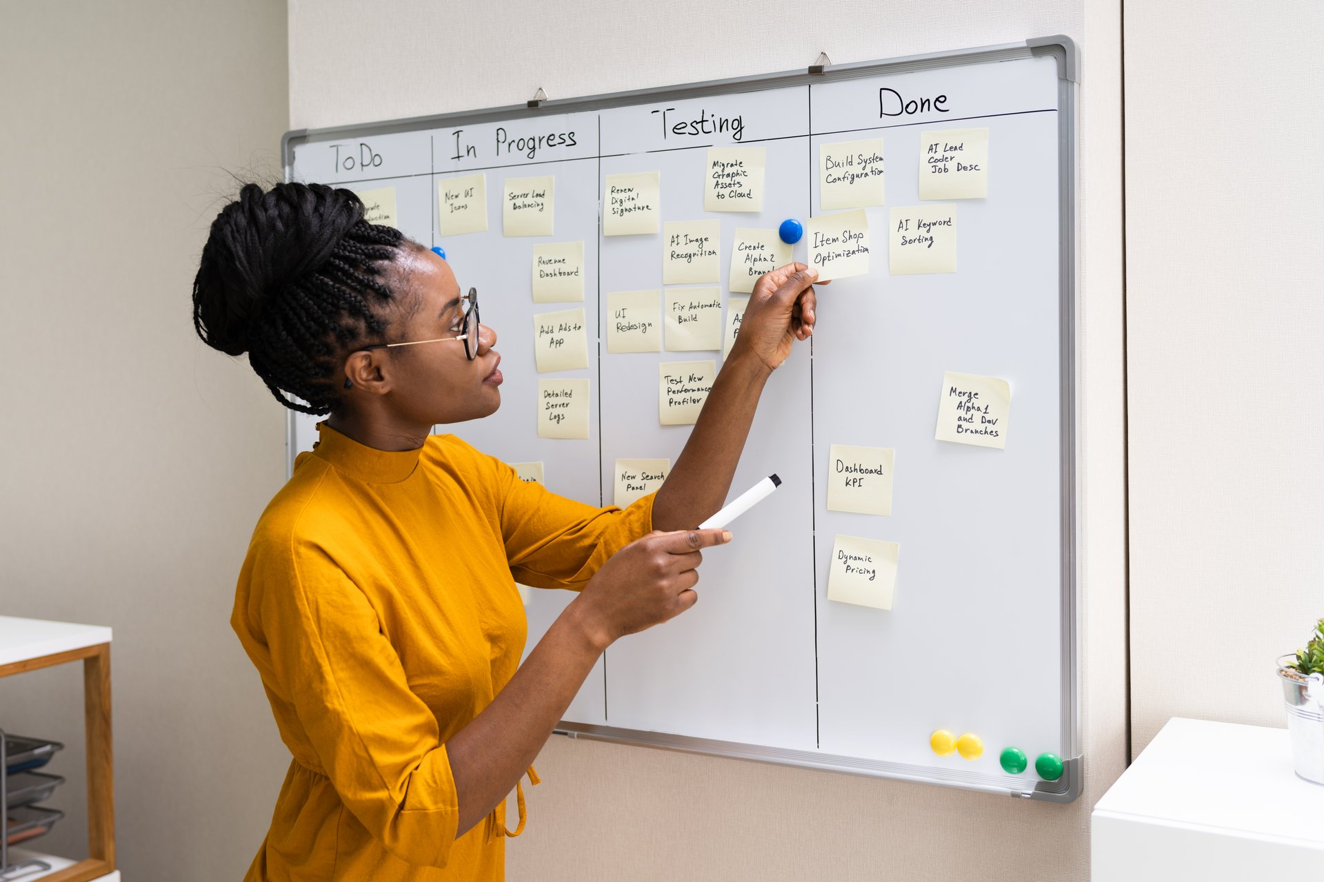 woman using stick notes on a whiteboard