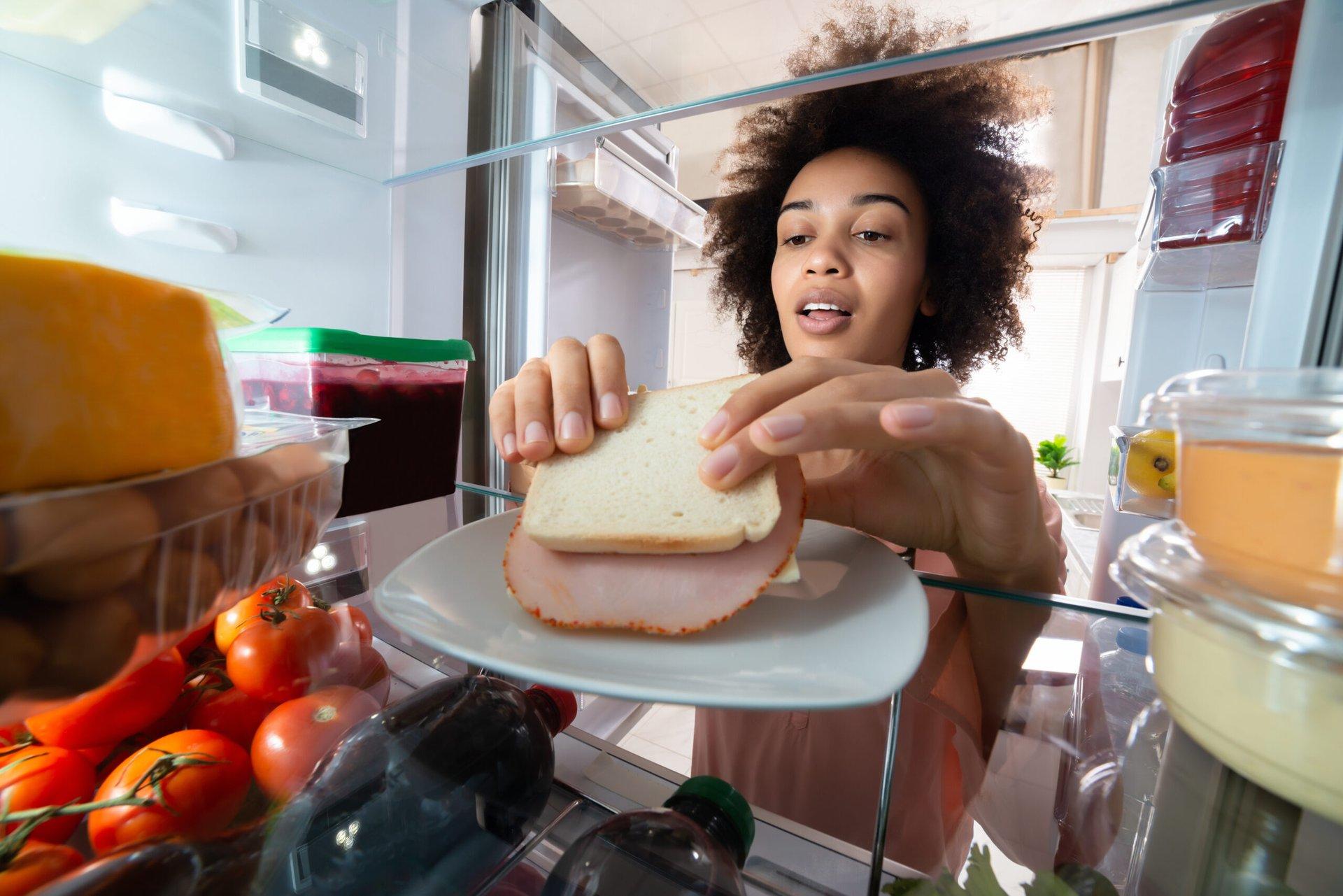 Woman eating ham sandwich