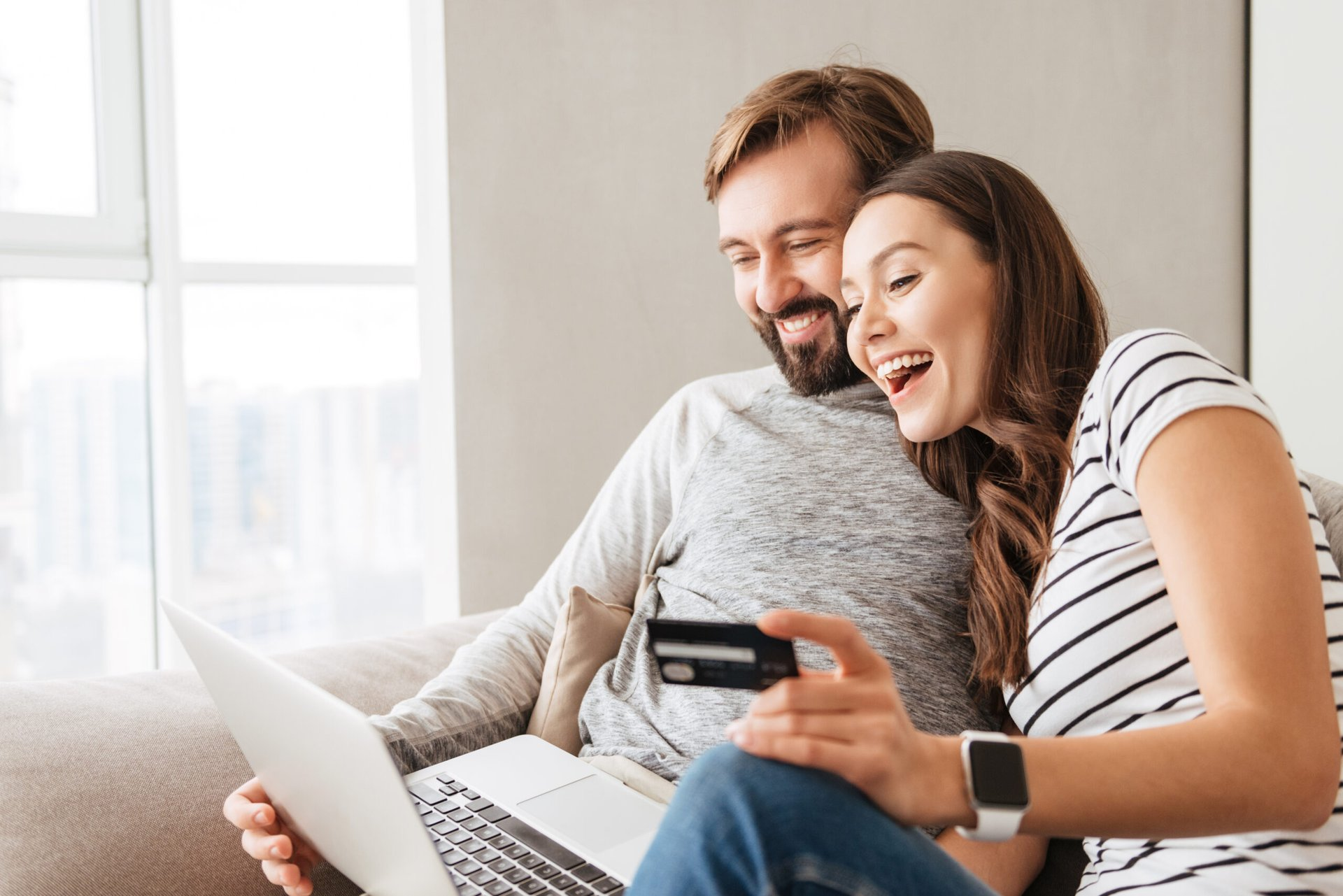 Happy couple using new credit card to shop online on laptop