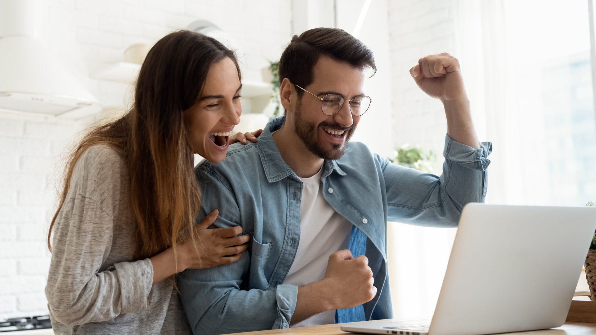 Excited millennial couple celebrating their online purchase at laptop