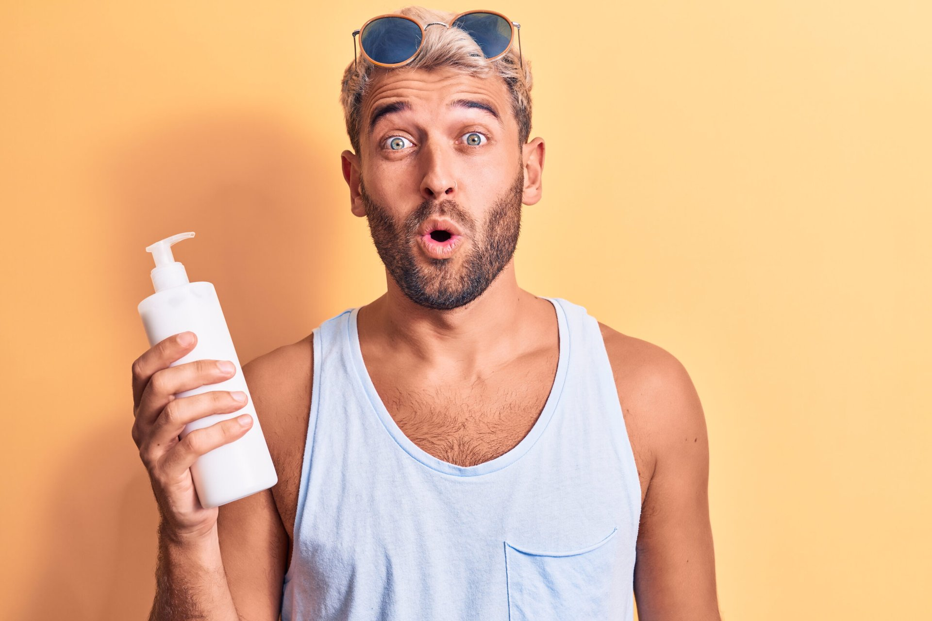 Man holding a bottle of sunscreen