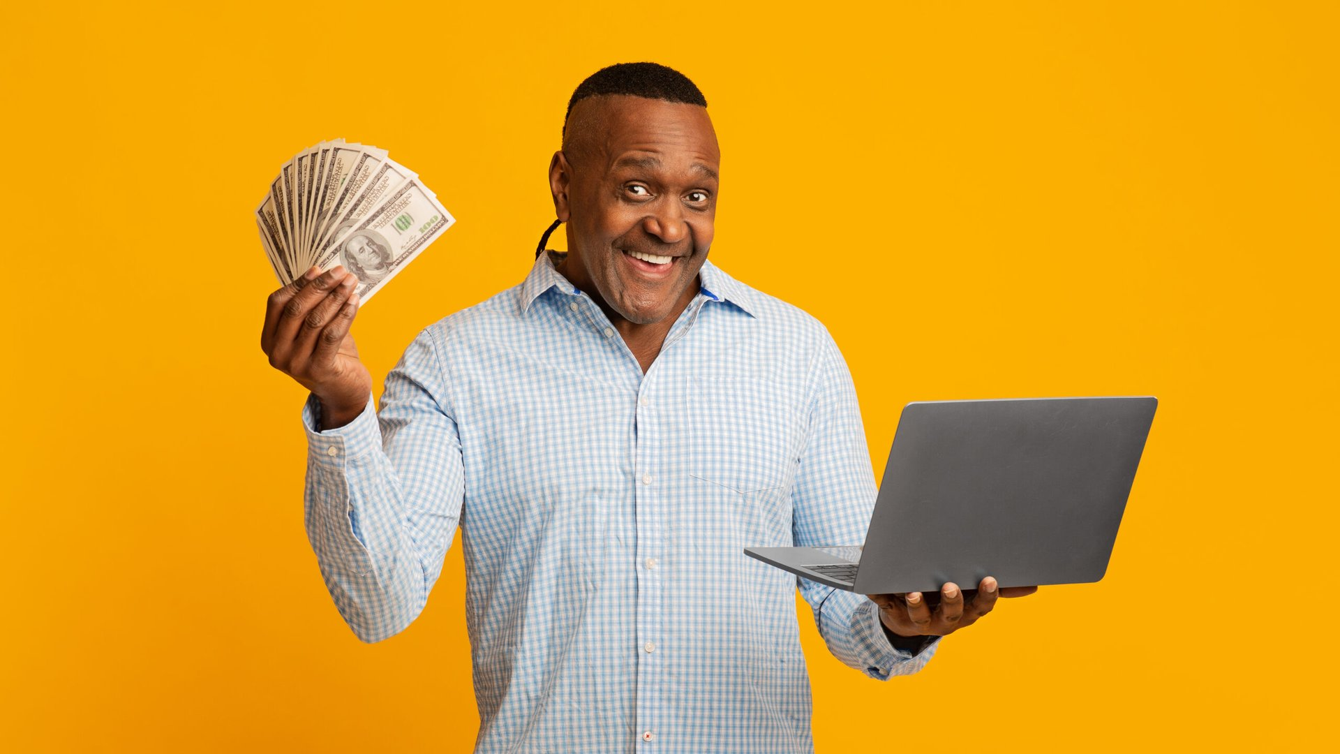 Excited man holding cash and a laptop computer