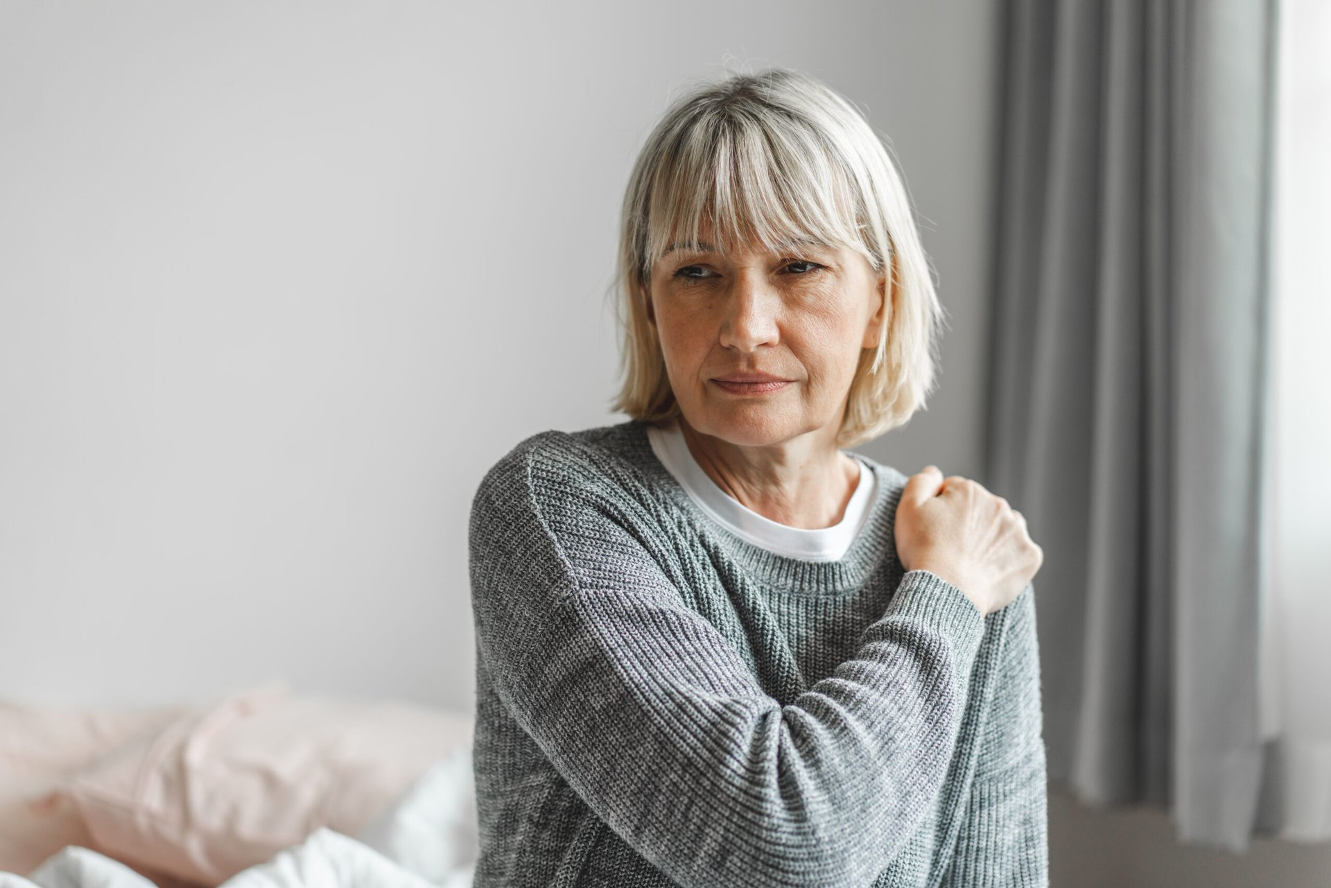 Woman holding her shoulder in pain
