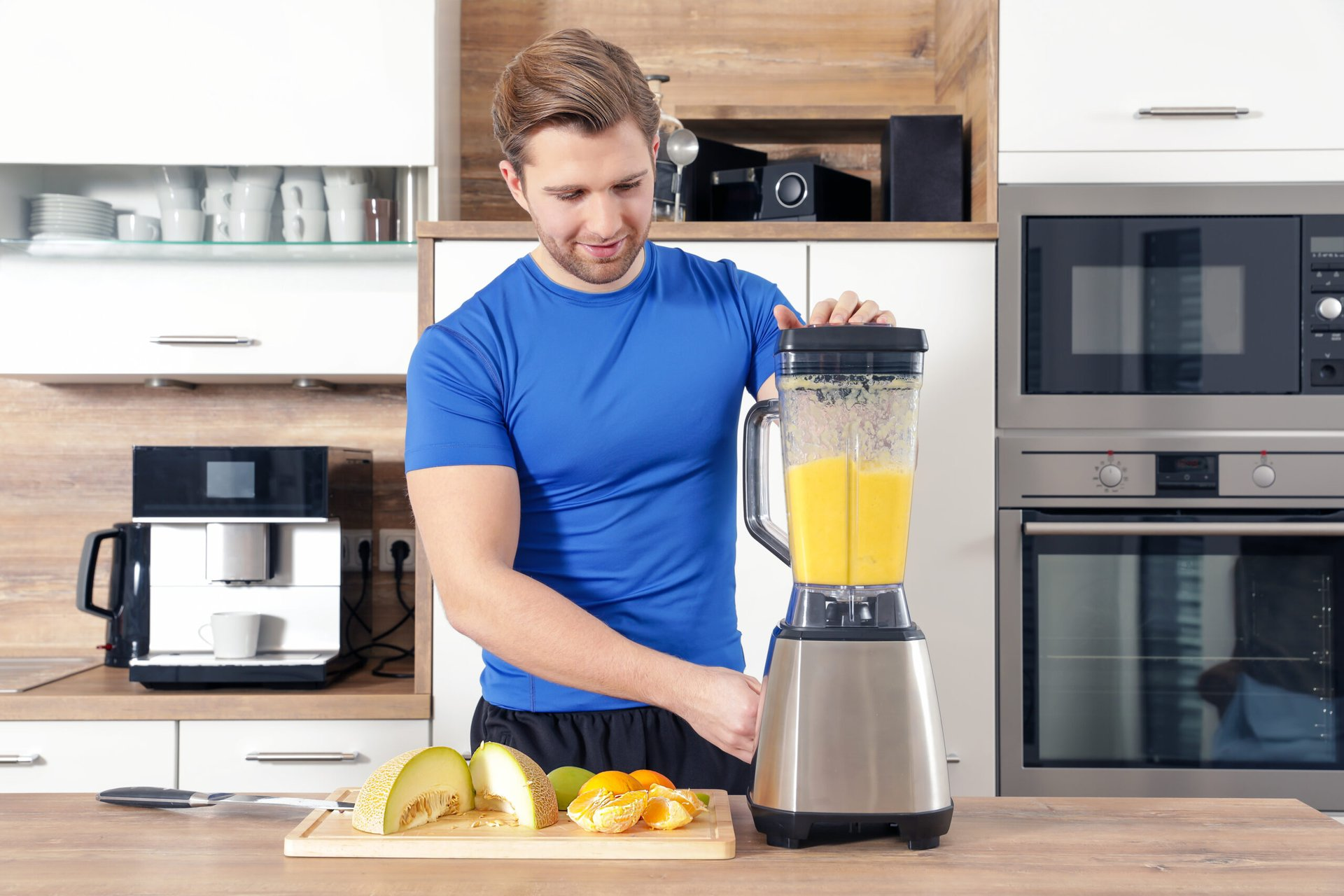 Man making a fruit smoothie in a blender