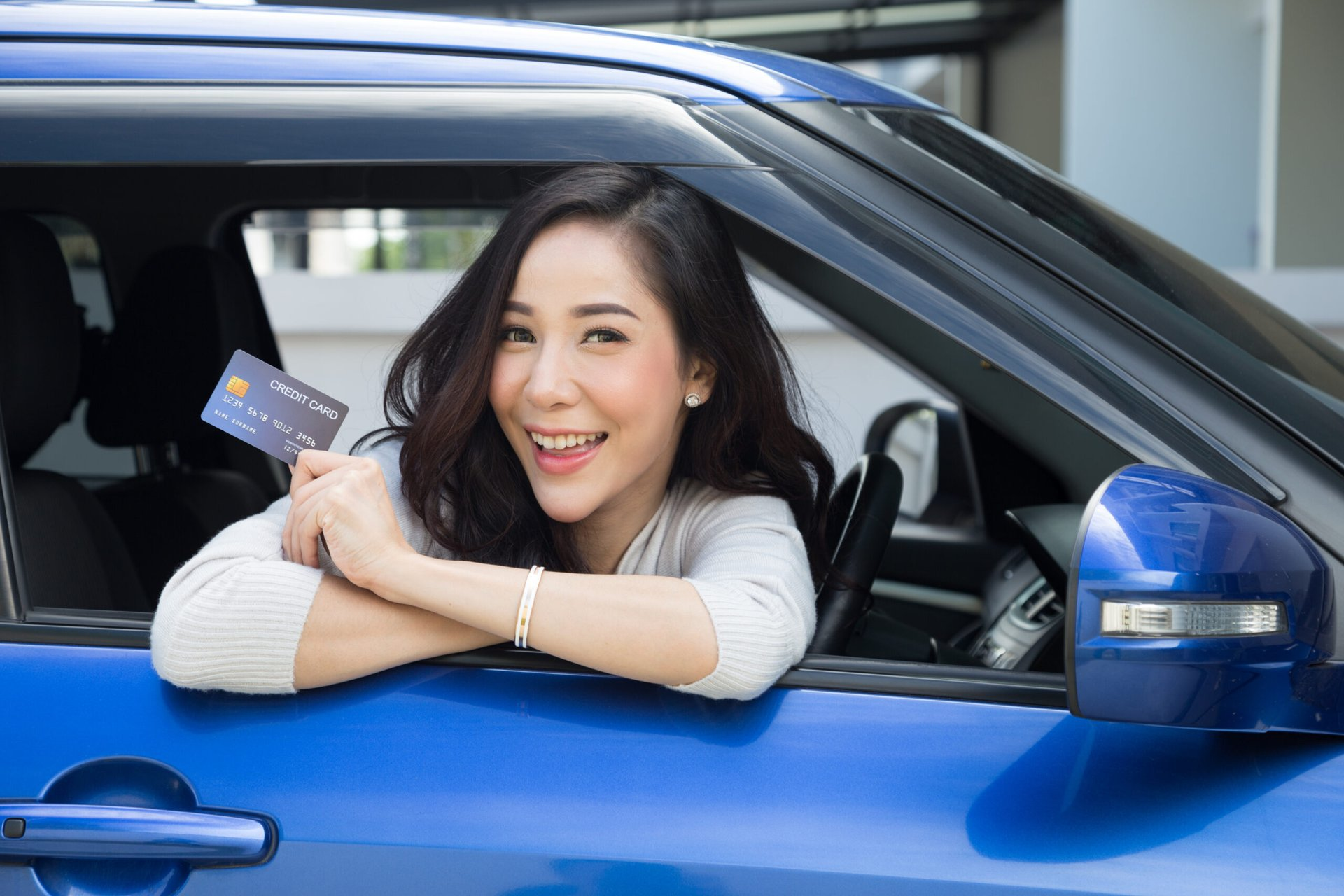 Woman in a car with a credit card