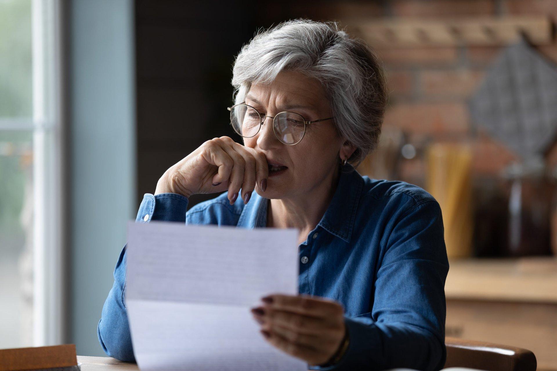 Upset senior holding a financial document