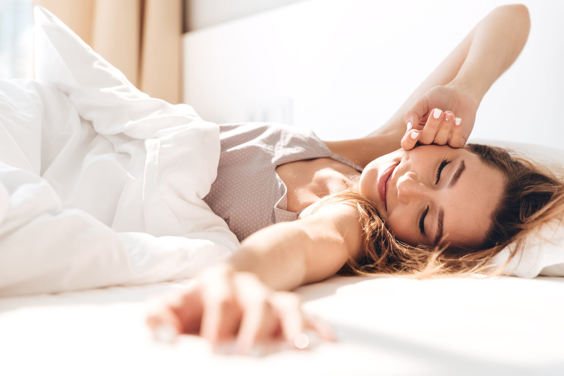 Happy woman sleeping peacefully in bed in the morning