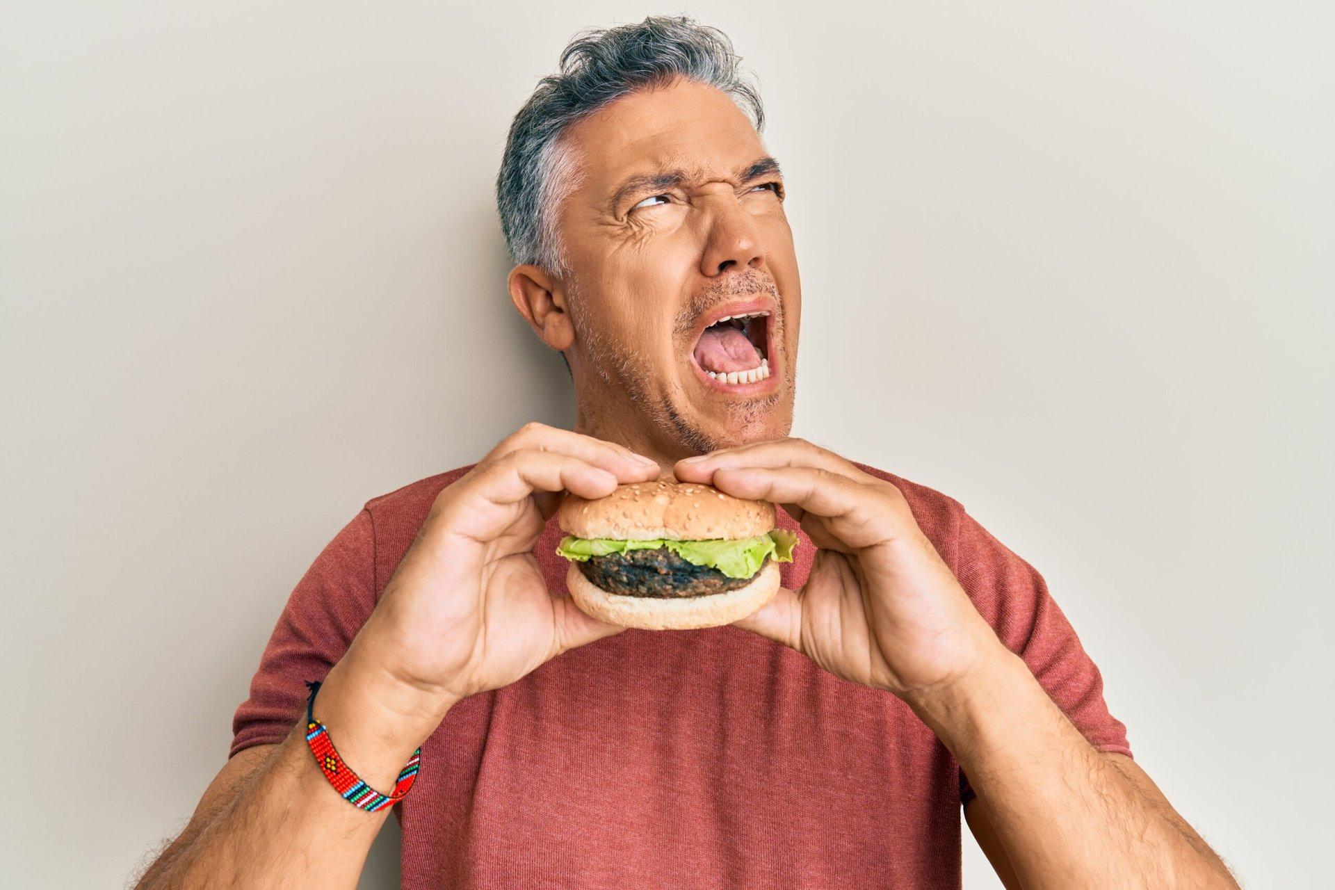 Unhappy man eating a burger