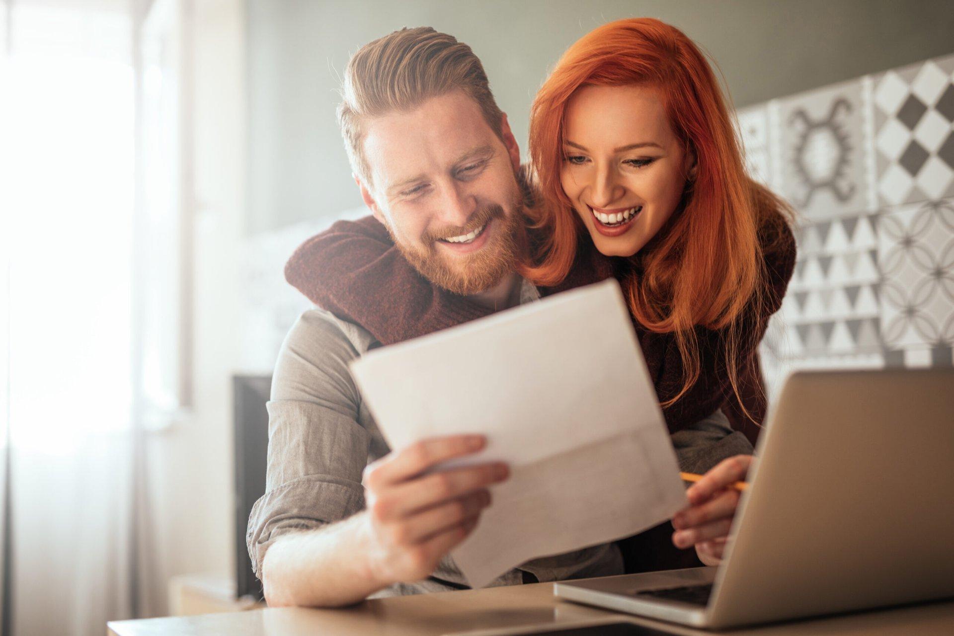 Happy couple looking at homeowners insurance savings