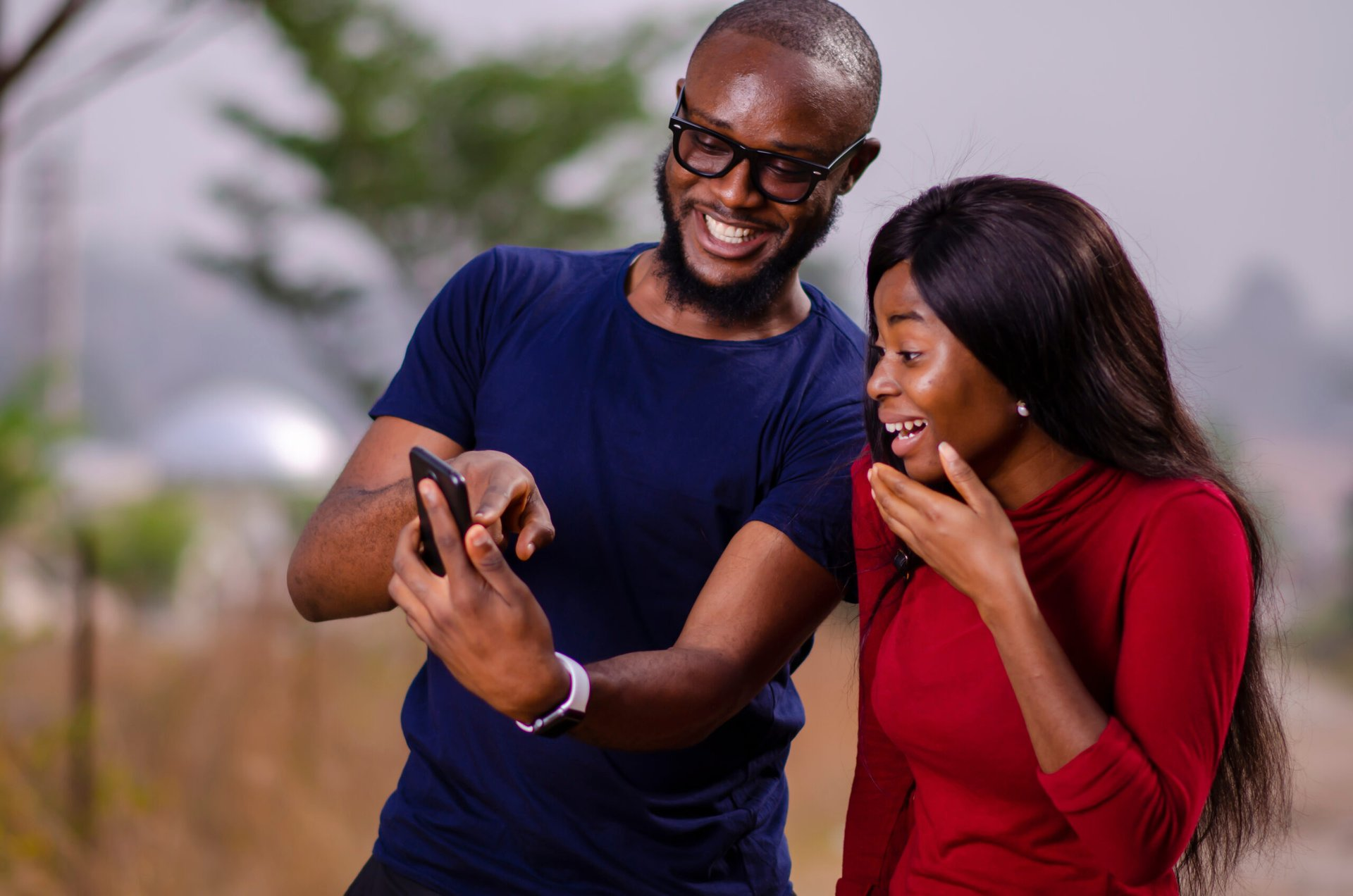 Man showing woman his great cellphone service on his smartphone