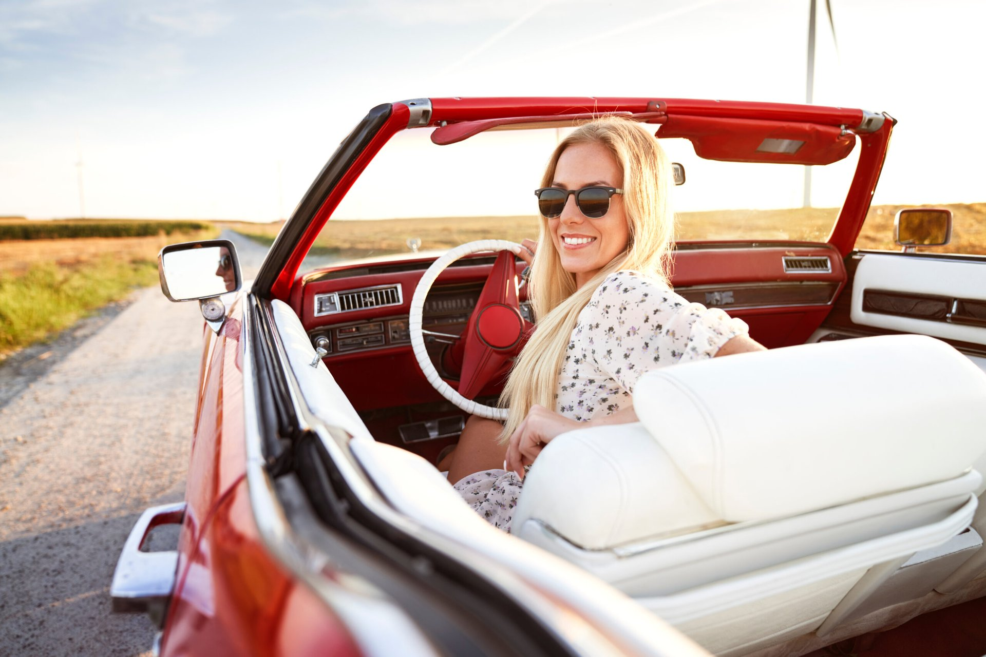 Happy beautiful woman behind the wheel of a red cadillac