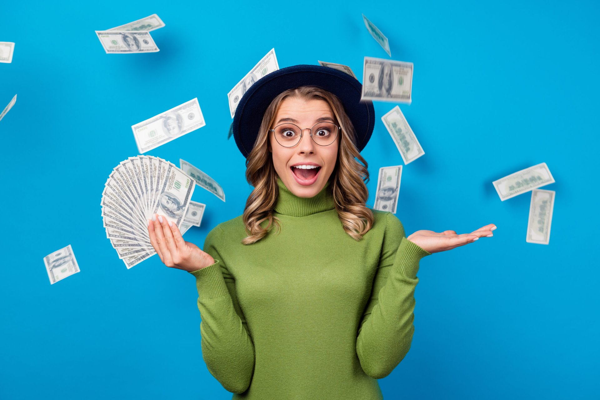 Excited woman holding lots of money and money raining from above