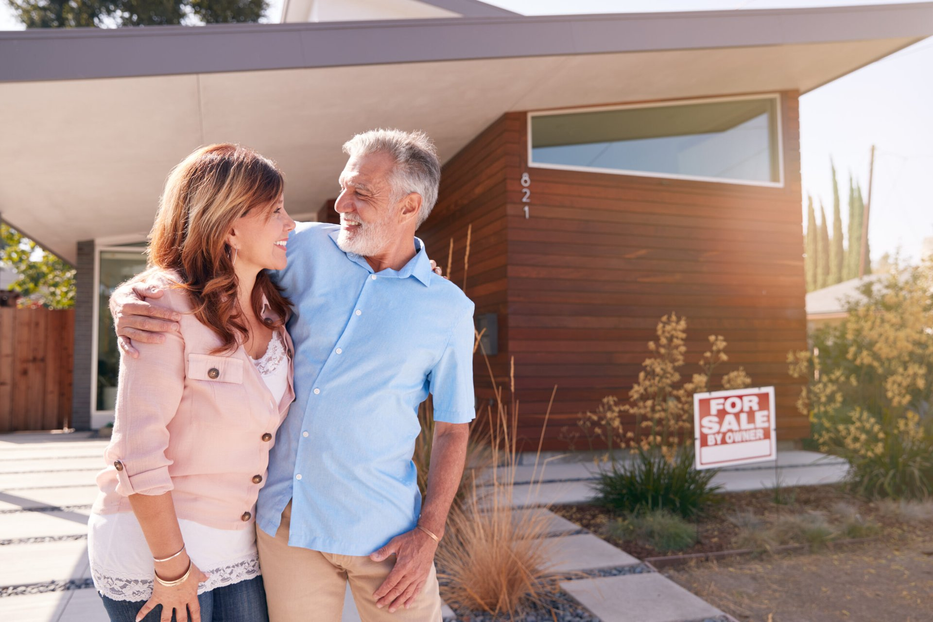 Older couple in front of a house for sale