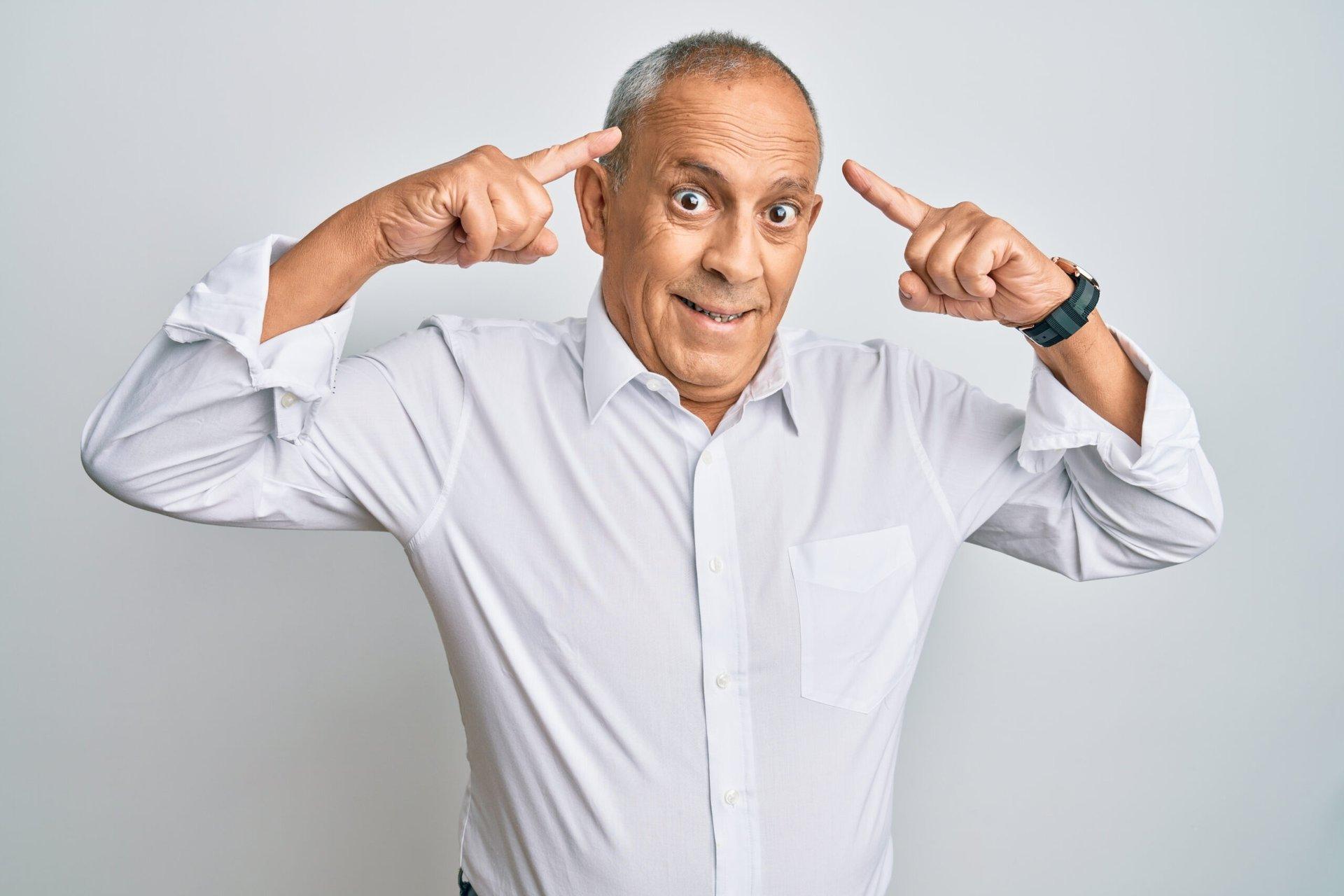 Senior man pointing to his head