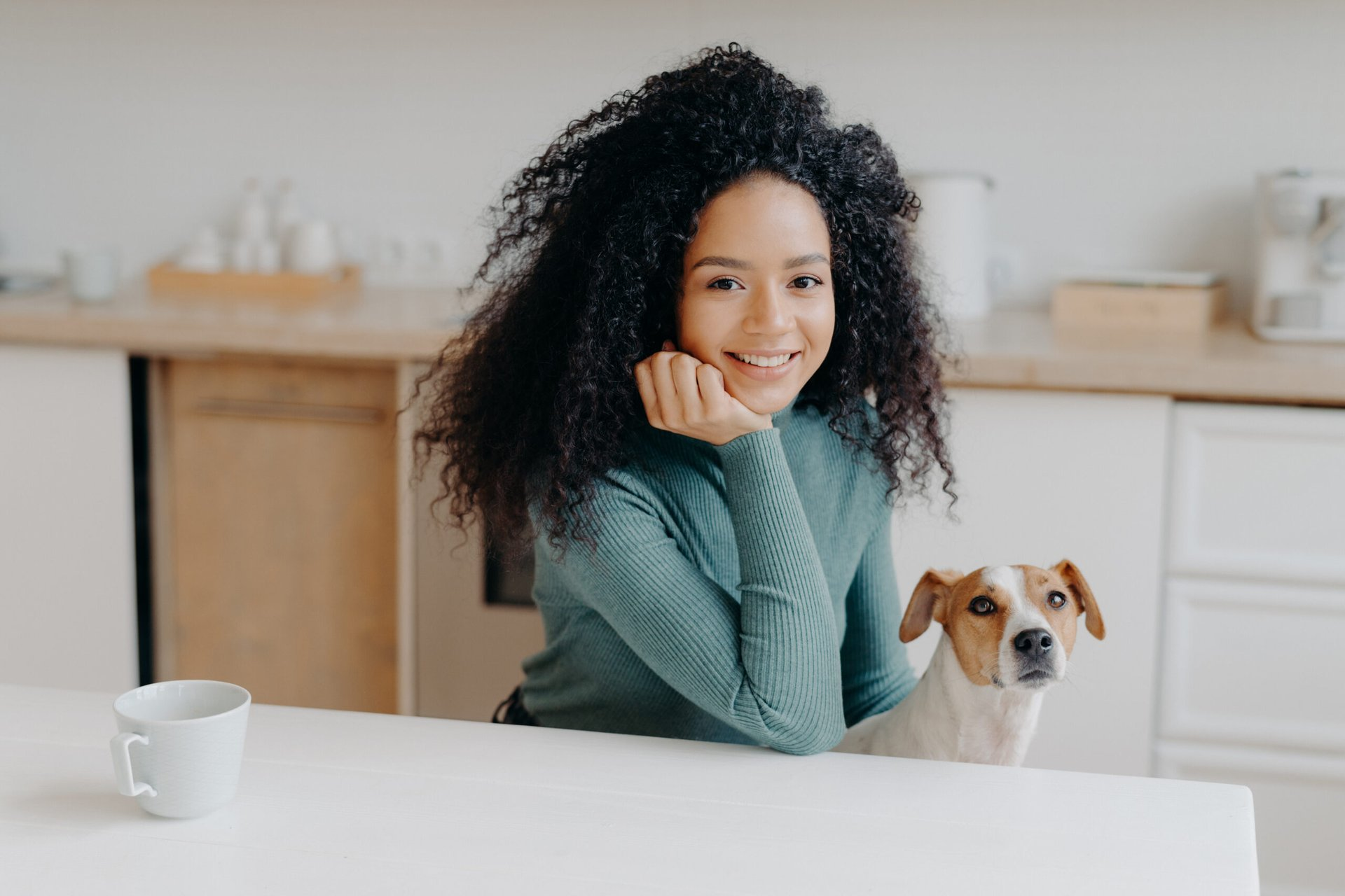 Woman sitting at her kitchen table with her dog