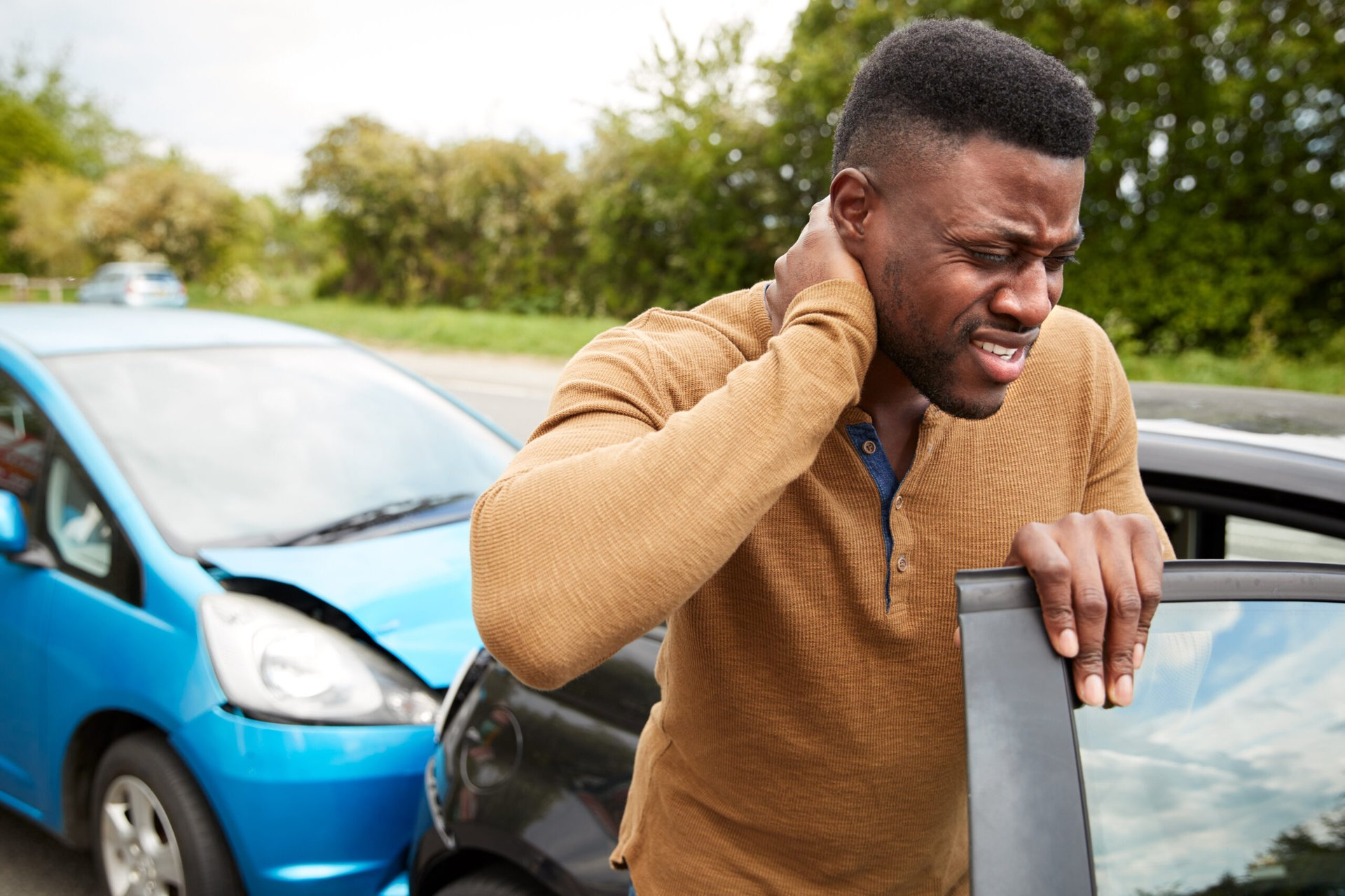 Man feeling neck after car accident