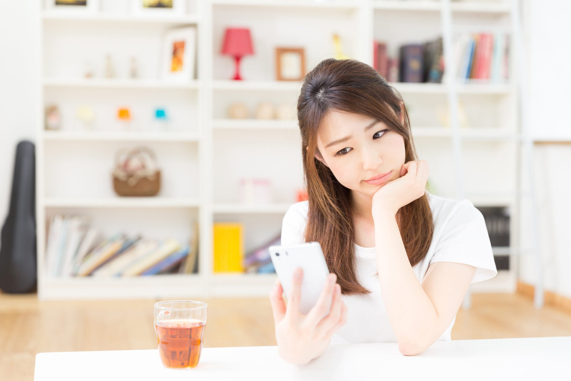 Young woman looking at her smartphone thoughtfully, considering lowering her bill