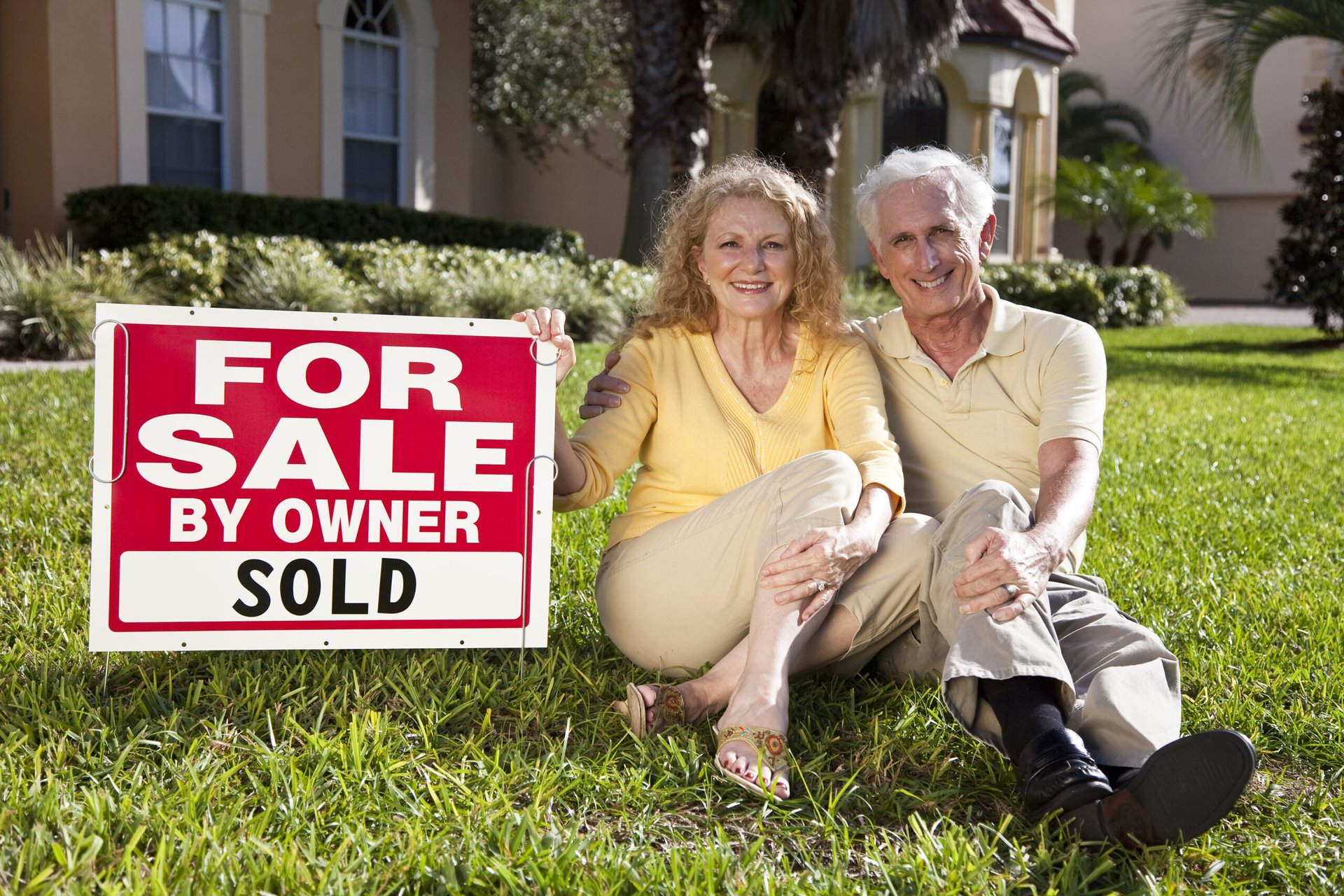 Older couple in front of their home they sold to downsize