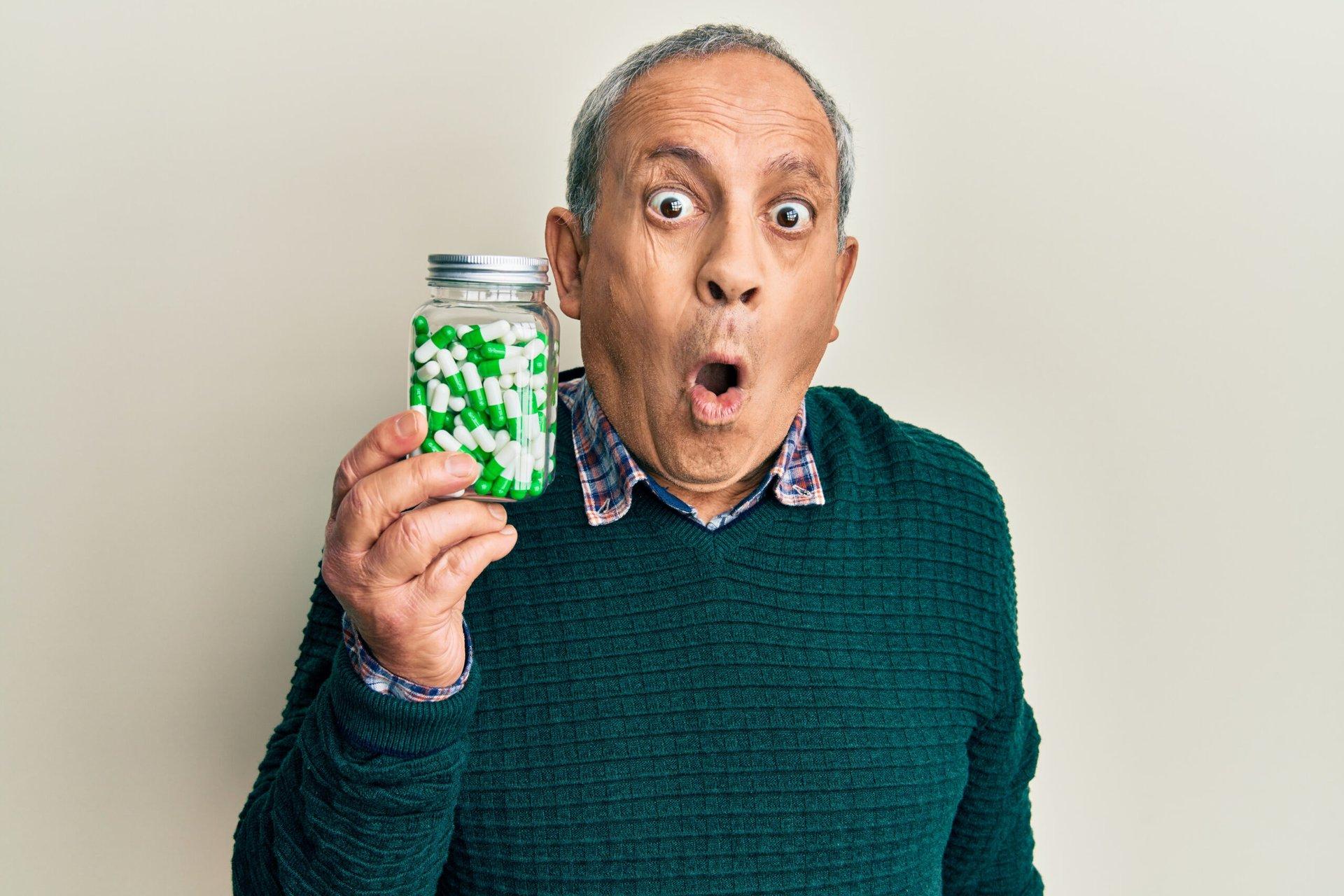 Frightened man holding bottle of pills