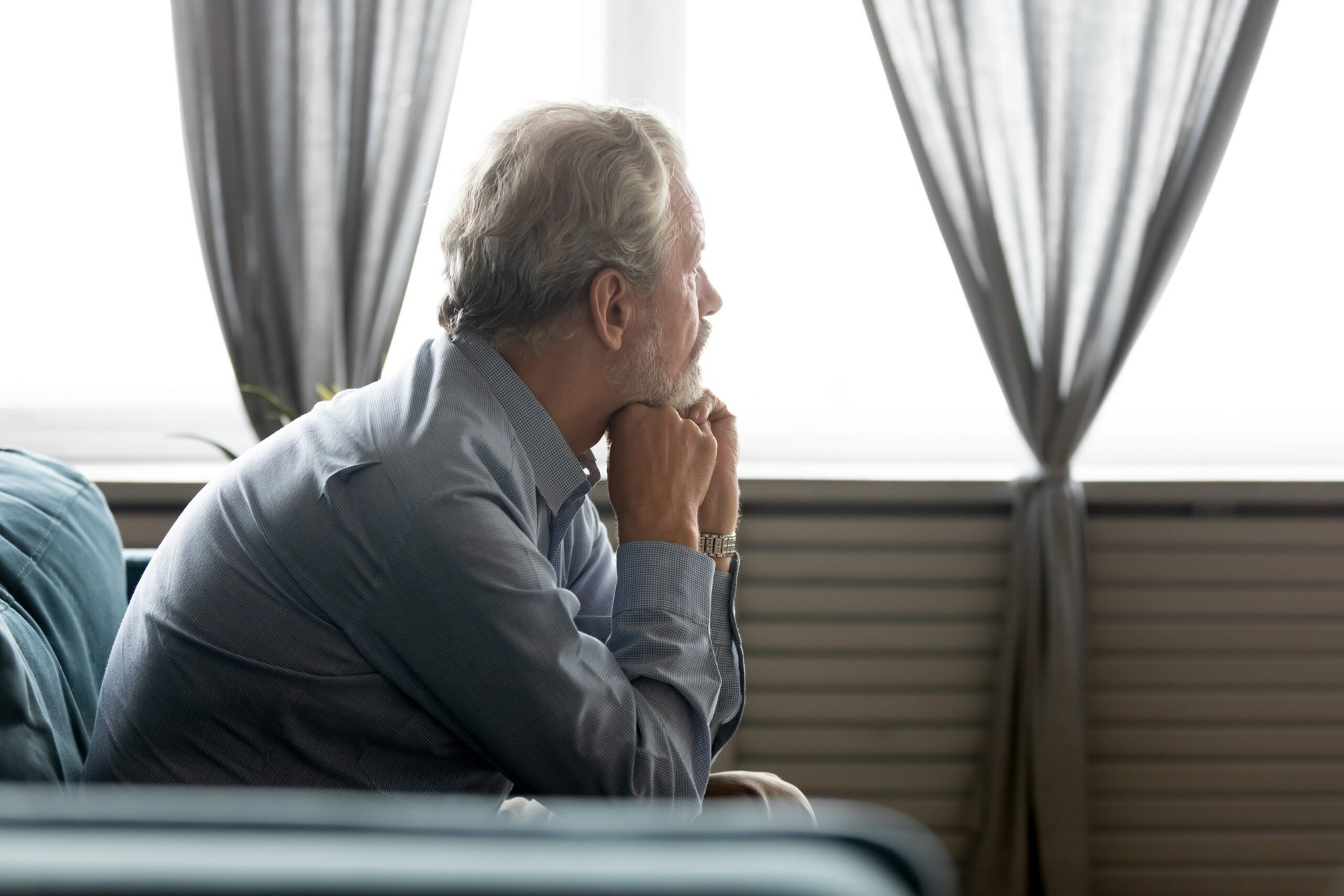 Sad senior looking out a window from his sofa