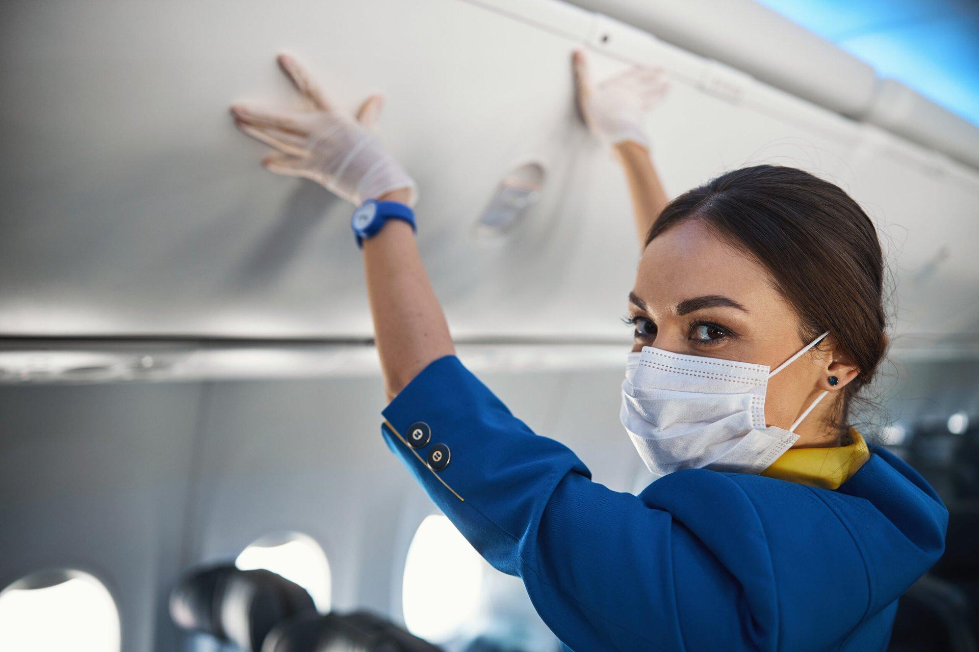 Flight attendant closing an overhead bin